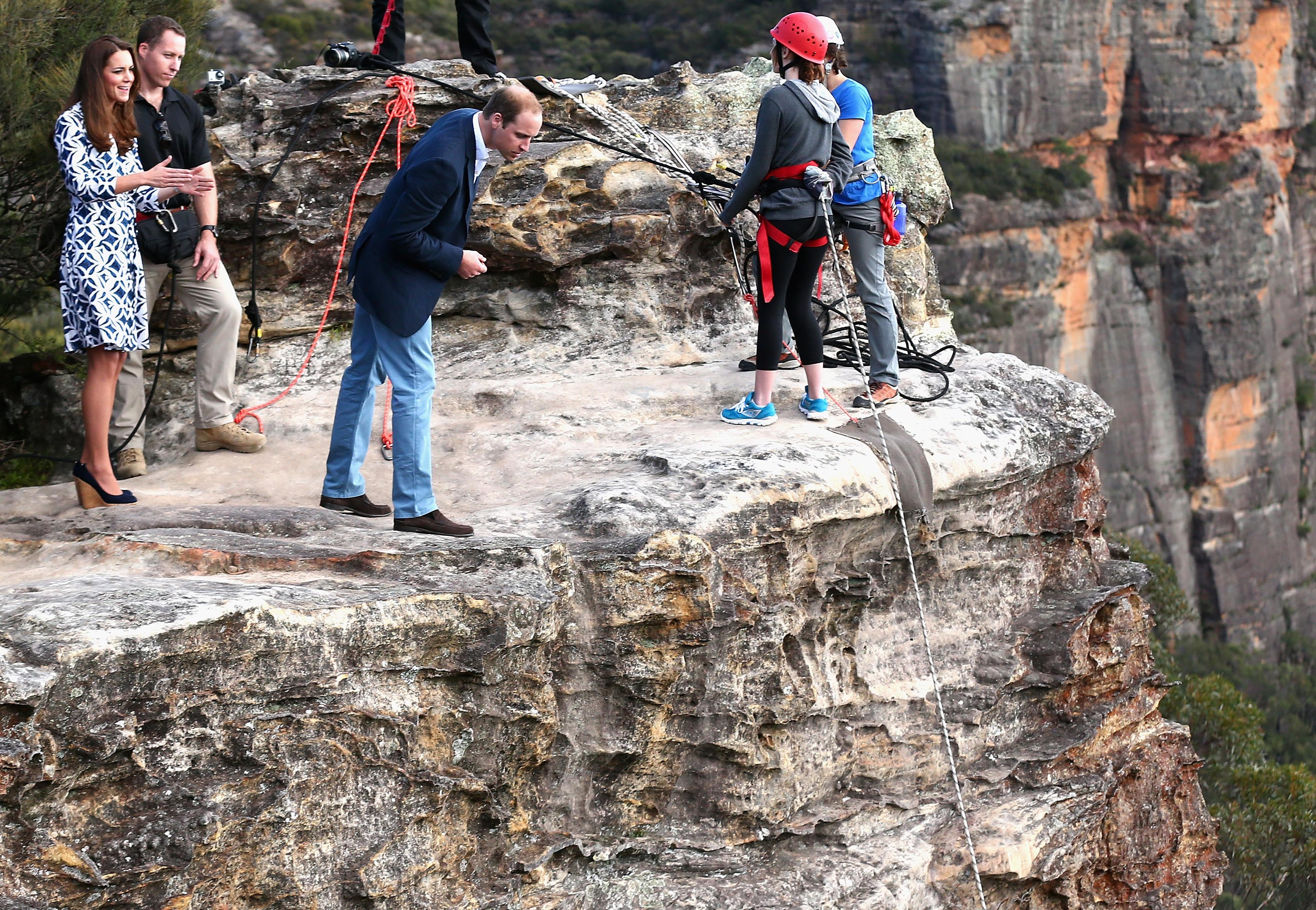 Britain's Prince William, third left, looks over the cliff edge as he and his wife Kate, the Duchess of Cambridge, left, observe abseiling and team building exercises at Narrow Neck Lookout near Katoomba, Australia, Thursday, April 17, 2014.