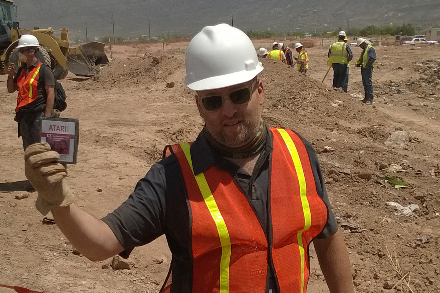 A member of the excavation team brandishes an E.T. cartridge  at a landfill in Alamogordo, New Mexico