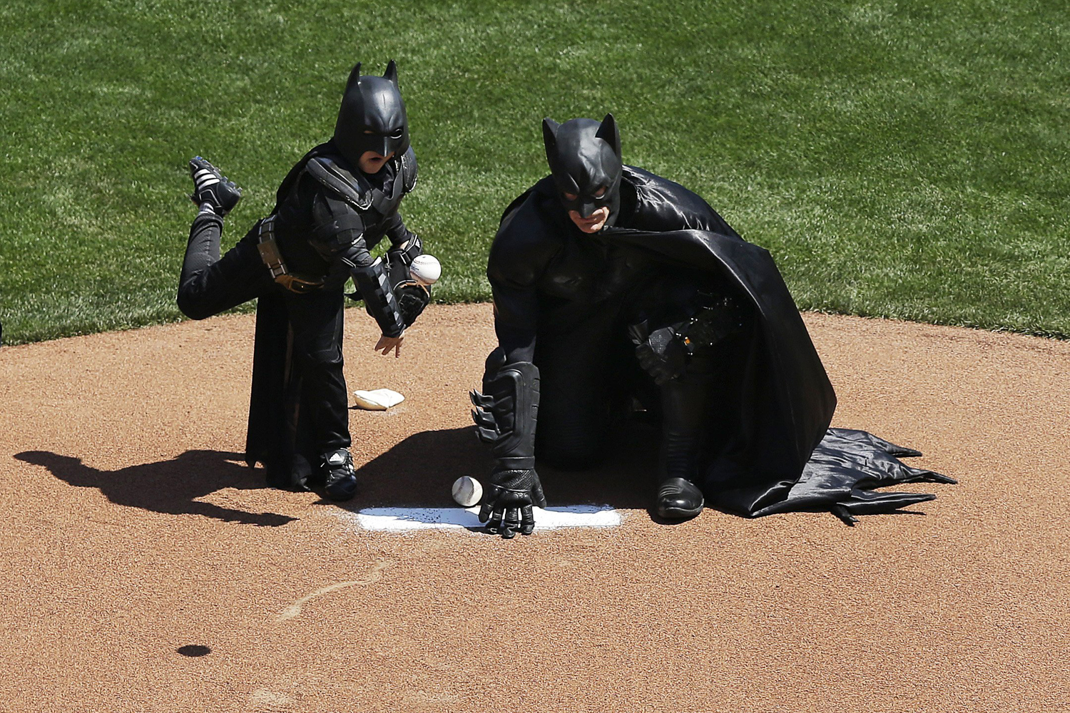 Apr. 8, 2014. Miles Scott, dressed as Batkid, left, throws the ceremonial first pitch next to Batman before an opening day baseball game between the San Francisco Giants and the Arizona Diamondbacks in San Francisco.
