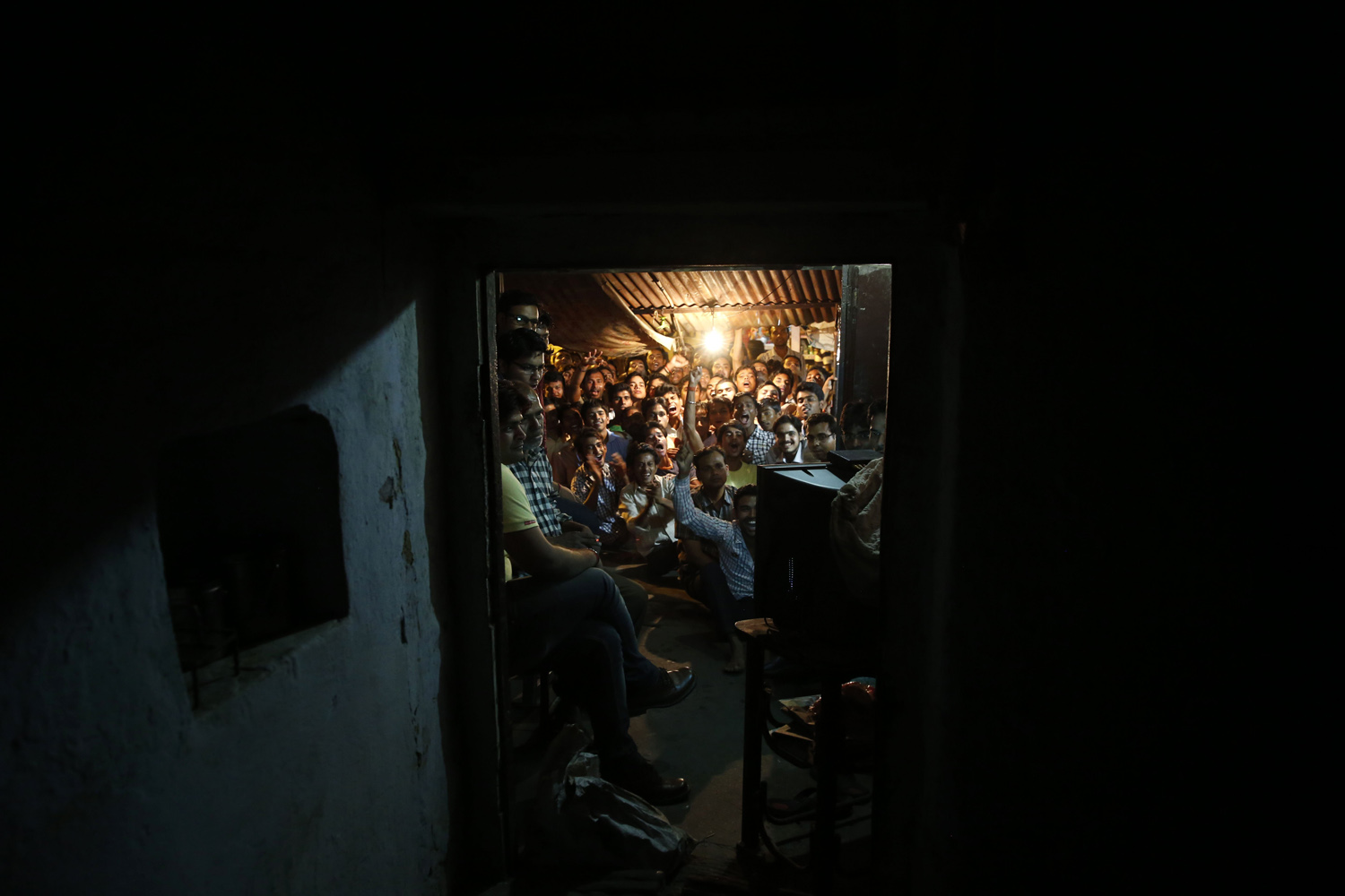 Apr. 6, 2014. Indian cricket fans celebrate as Virat Kohli plays a shot  in the ICC Twenty20 Cricket World Cup final match between India and Sri Lanka while watching on a television set at a roadside shop in Allahabad, India.