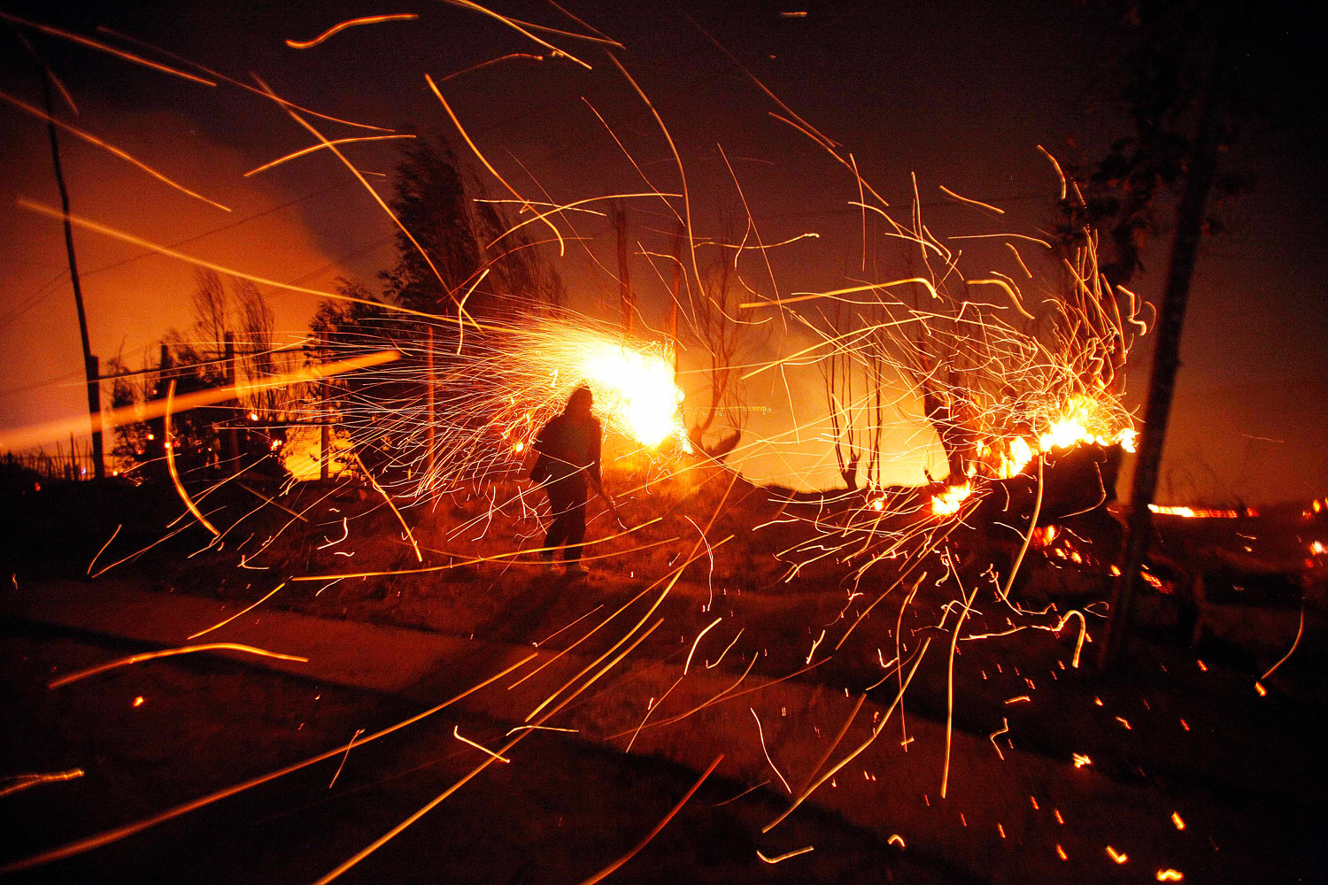 A person tries to extinguish flames as sparks fly, April 13, 2014.