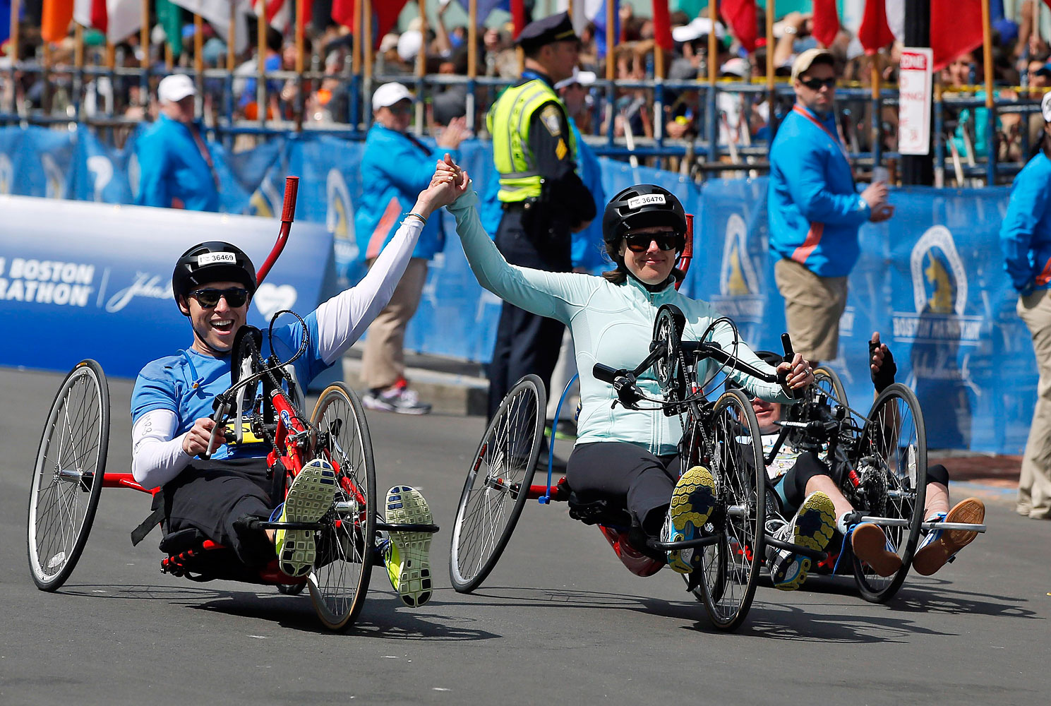 Boston Marathon husband and wife bombing survivors Patrick Downes and Jessica Kensky, who each lost a leg in last year's bombings, roll across the finish line in the 118th Boston Marathon, April 21, 2014 in Boston.