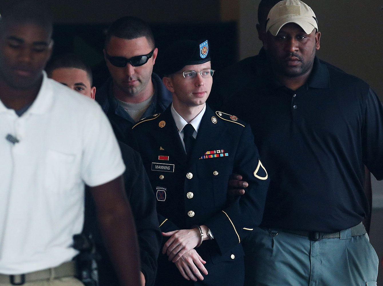 Bradley Manning, now known as Chelsea Manning, being escorted out of a military-court facility in Fort Meade, Md., on Aug. 20, 2013
