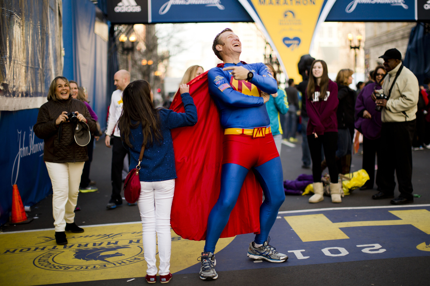 Trent Morrow of Sydney, Australia, also know as  Marathon Man  laughs as Andrea Olivo of Venezuela tugs on his cape as she has her photo made ahead of Monday's 118th Boston Marathon, Sunday, April 20, 2014.