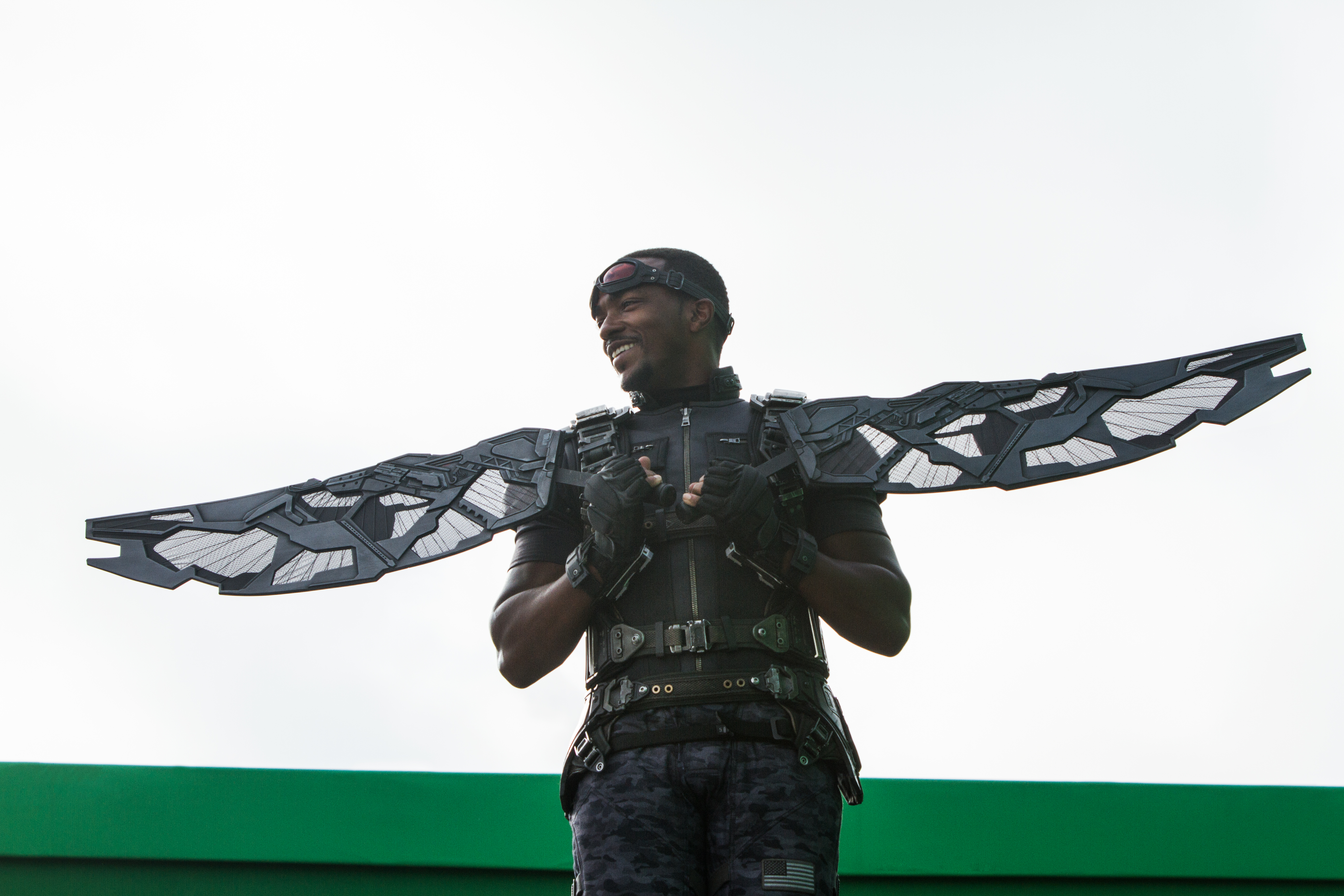 """Mackie holds up mockup """"Falcon"""" wings which will be replaced in post-production with computer graphics."""
