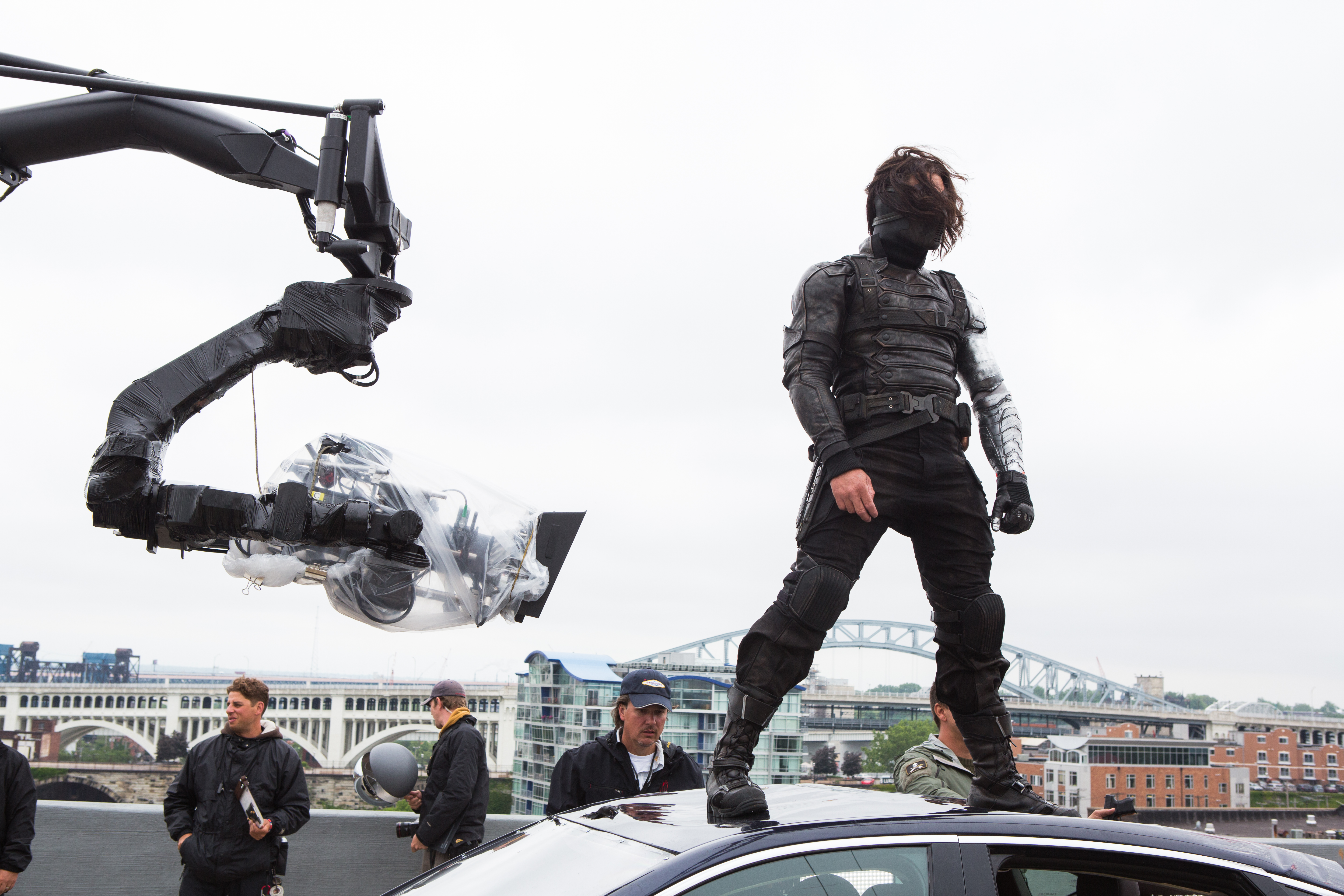 Sebastian Stan stands on top of a car on set.