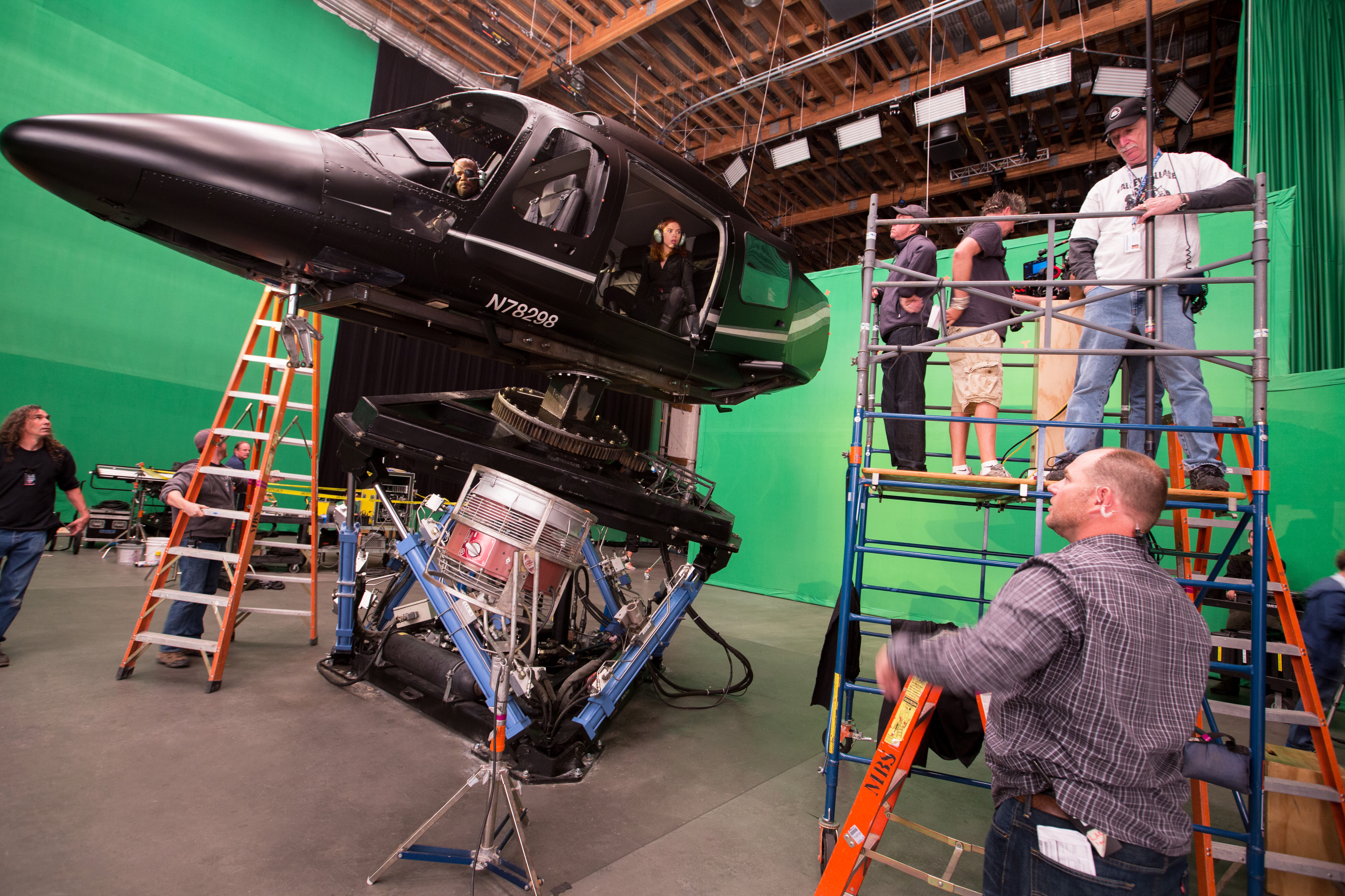 Samuel L. Jackson as Nick Fury and Scarlett Johansson as Black Widow fly a mock helicopter in front of a green screen.