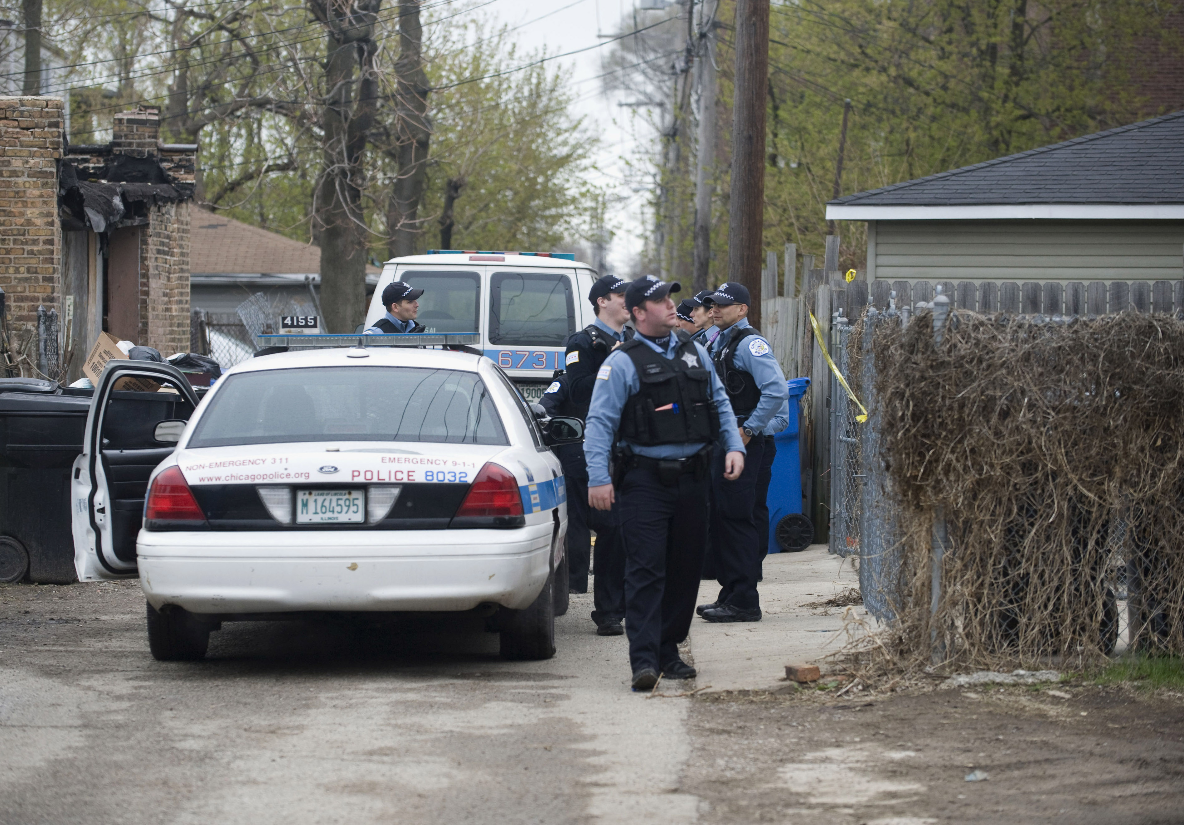 Police stand outside a residence in Chicago after a 14-year-old girl was fatally shot and another girl wounded in the Back of the Yards neighborhood in Chicago, April 28, 2014.