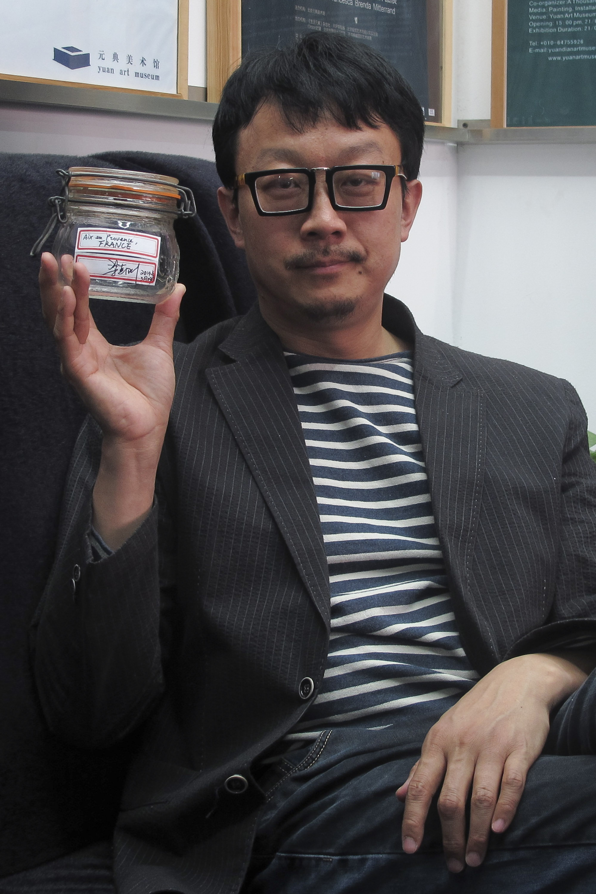 Beijing artist Liang Kegang is pictured with the jar of fresh air collected in Provence, France, in an art gallery in Beijing, China.