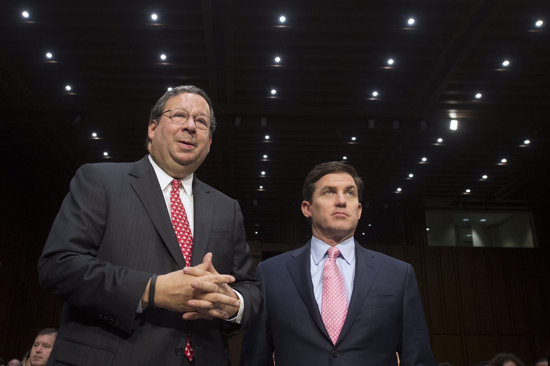 From left: David Cohen, executive vice president of the Comcast Corporation, speaks with Arthur Minson Jr., executive vice president and CFO of the Time Warner Cable Inc., before the start of a Senate Judiciary Committee hearing on Capitol Hill in Washington, April 9, 2014.