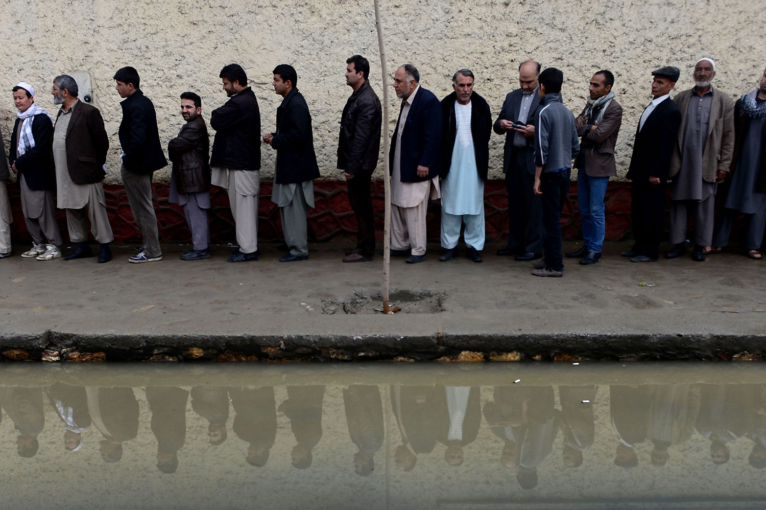 Afghan residents wishing to vote line up outside a local polling station in Kabul.