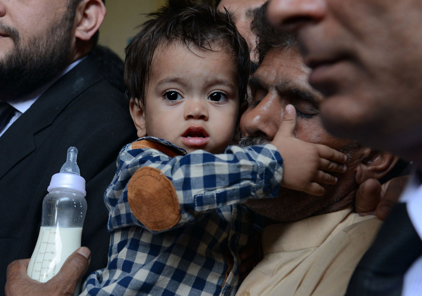 Nine month Pakistan toddler Mohammad Musa is held by his grandfather Muhammad Yasin for a court hearing in Lahore on April 12, 2014.
