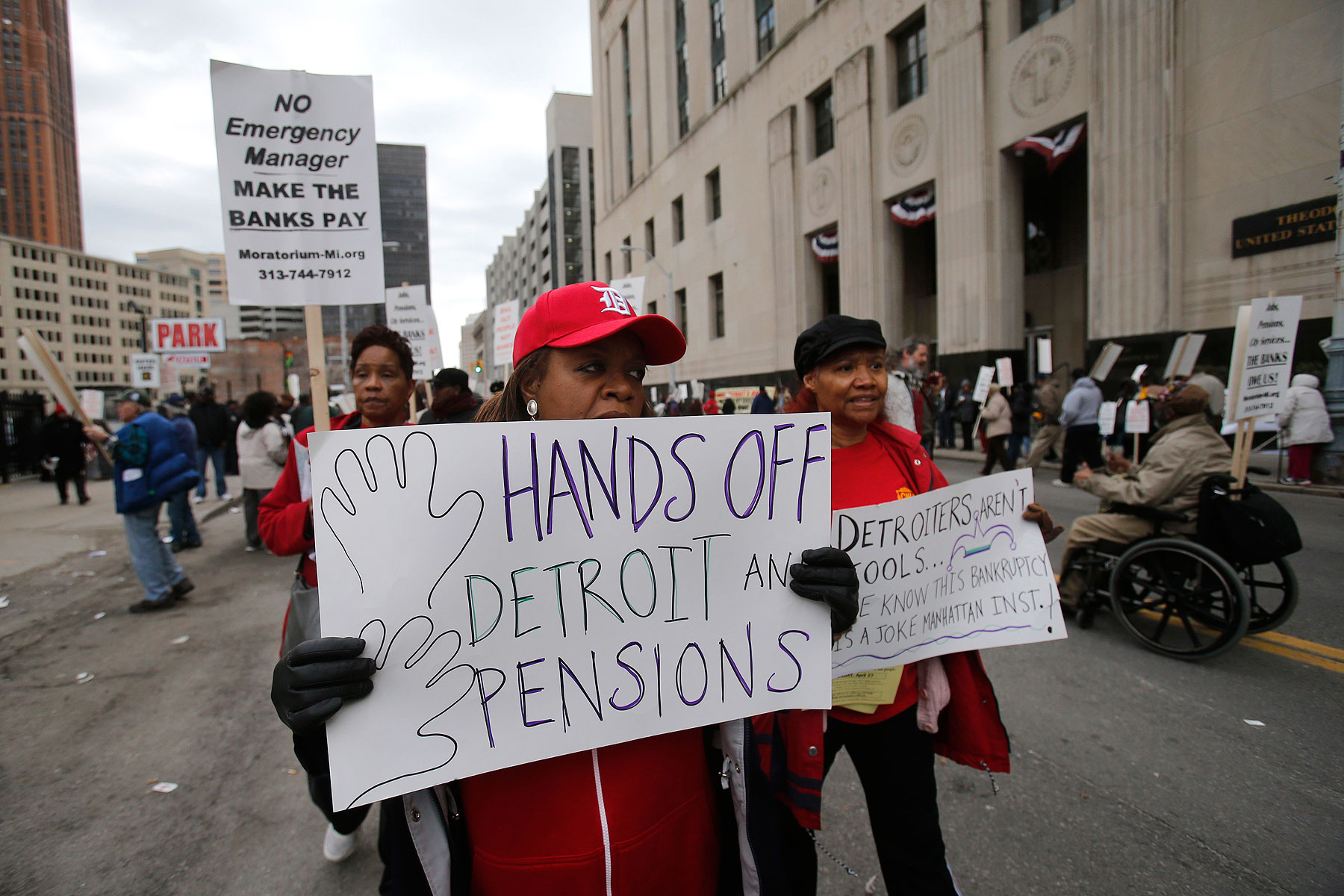 A protestor holds a sign outside the federal courthouse in support of Detroit city workers