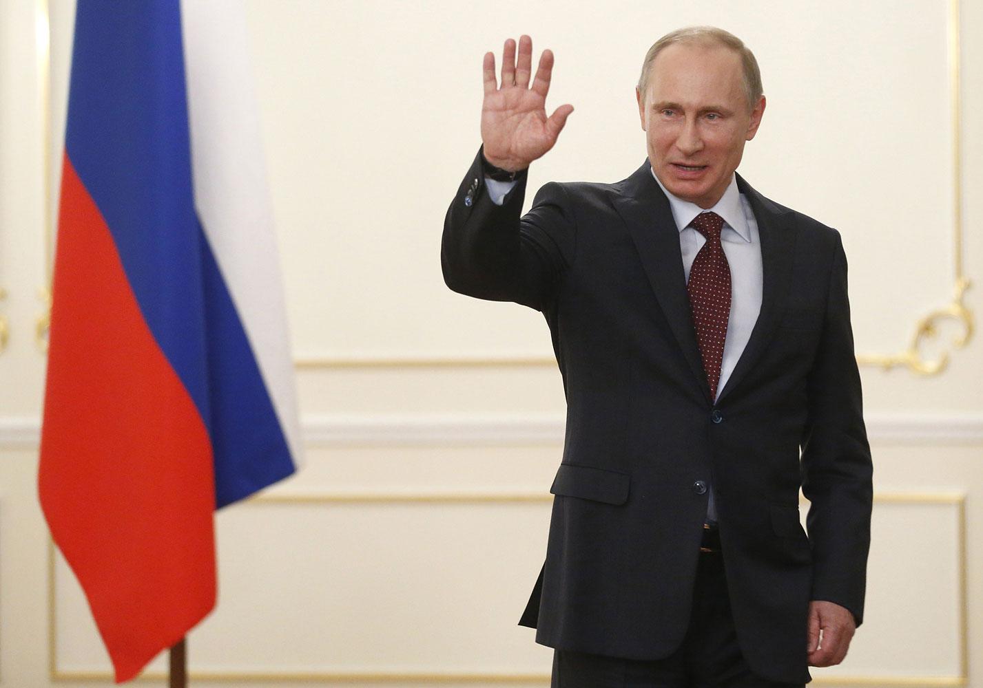 Vladimir Putin waves in his Novo-Ogaryovo residence outside Moscow, on April 18, 2014.