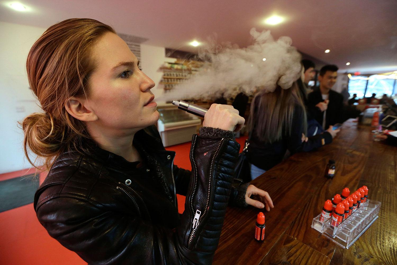 Talia Eisenberg, co-founder of the Henley Vaporium, uses her vaping device in New York, Feb. 20, 2014.
