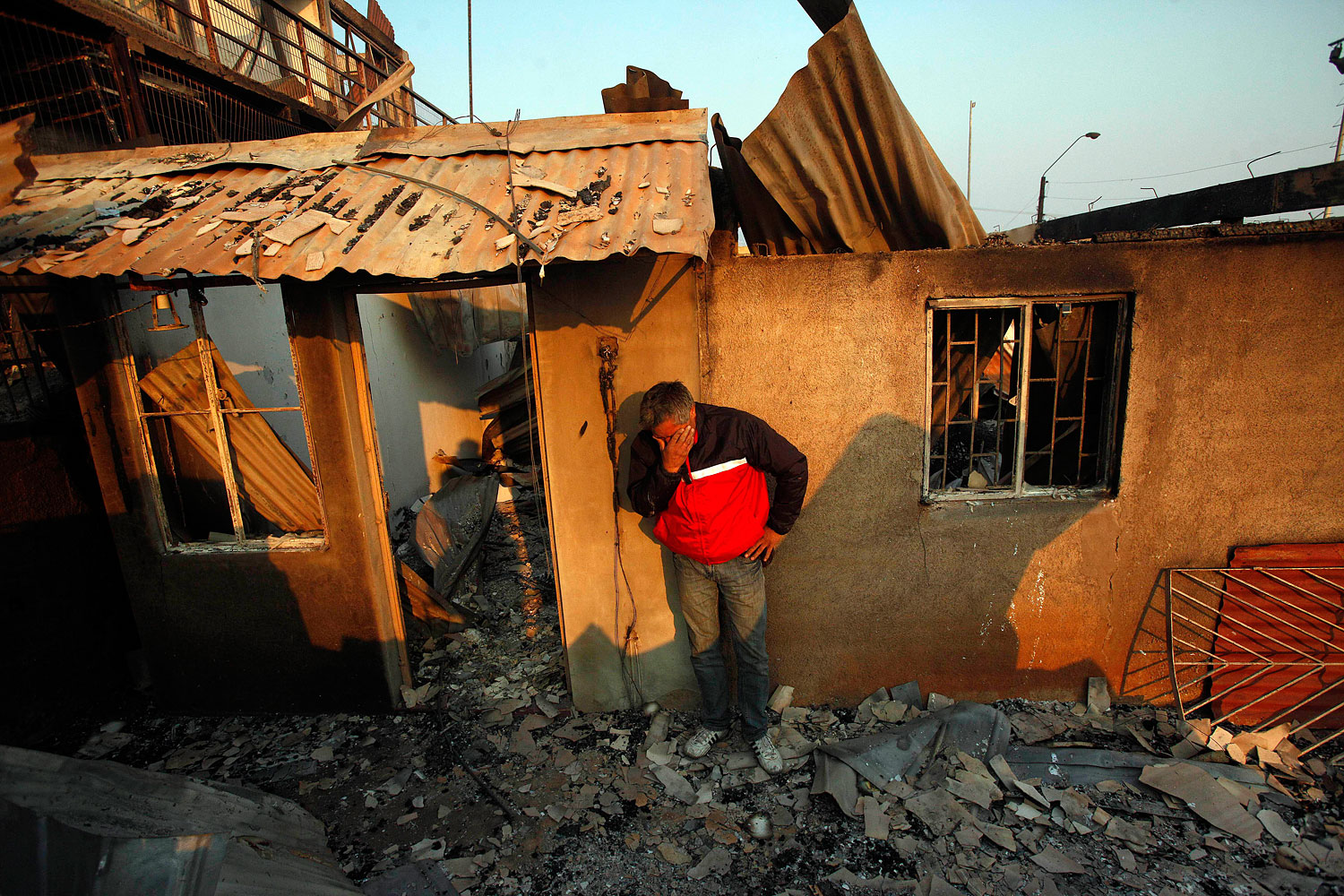 A man cries next to the remains of his house, April 13, 2014.