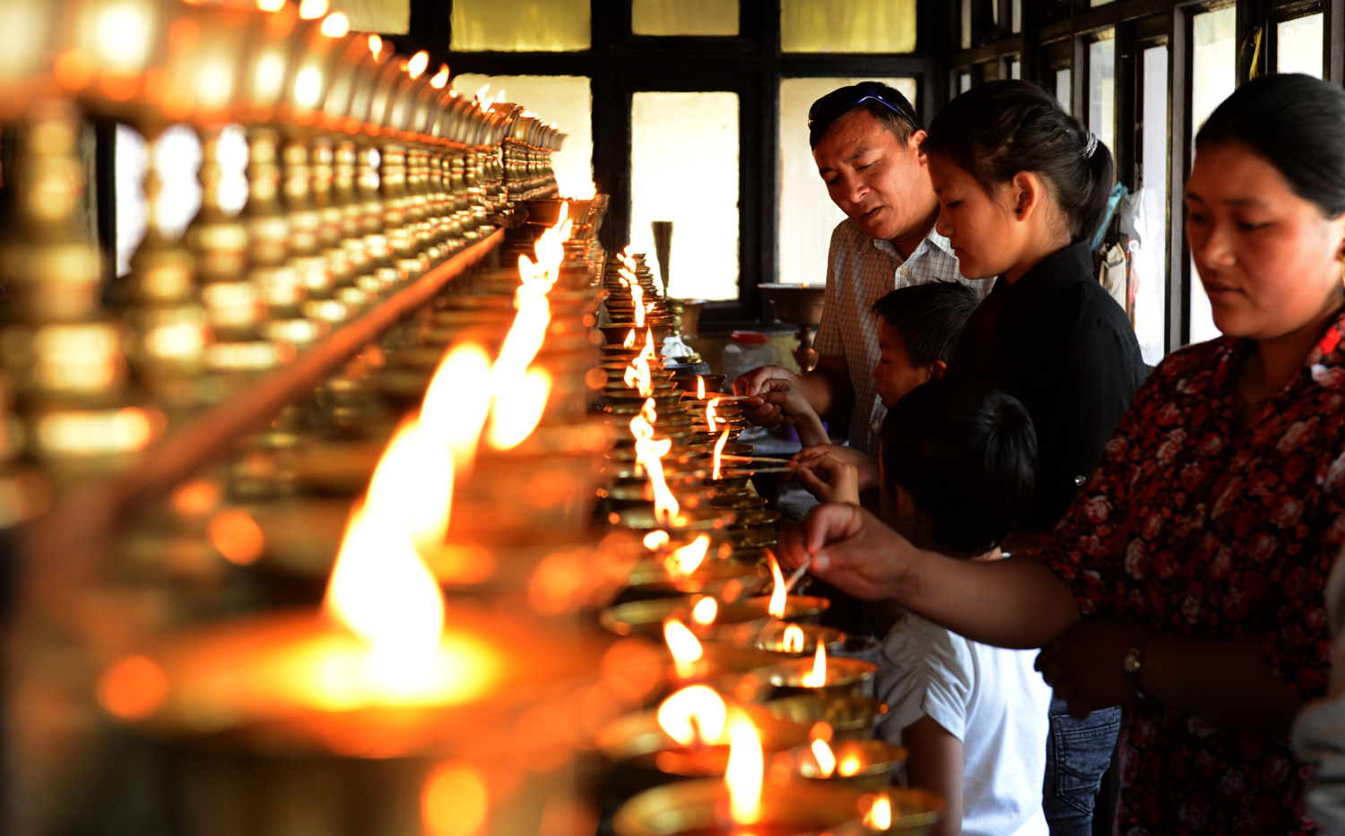 Family members of the Everest avalanche victims light oil lamps at Sherpa Monastery in Kathmandu on April 20, 2014. Nepal has called off the search for three local guides still missing, citing weather conditions