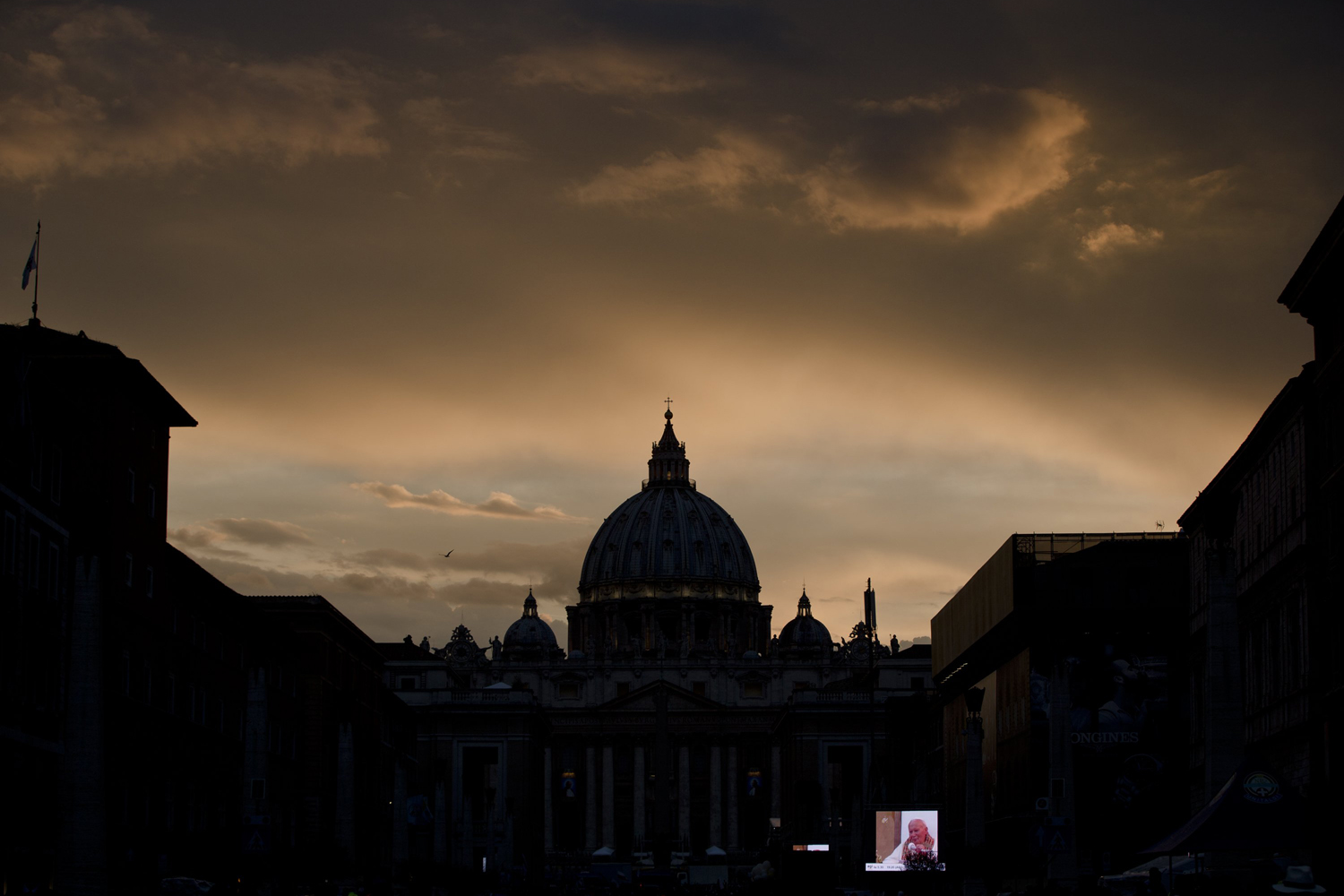 Apr. 26, 2014. A large screen for public display shows Pope John Paul II after sunset outside St. Peter's Square at the Vatican.