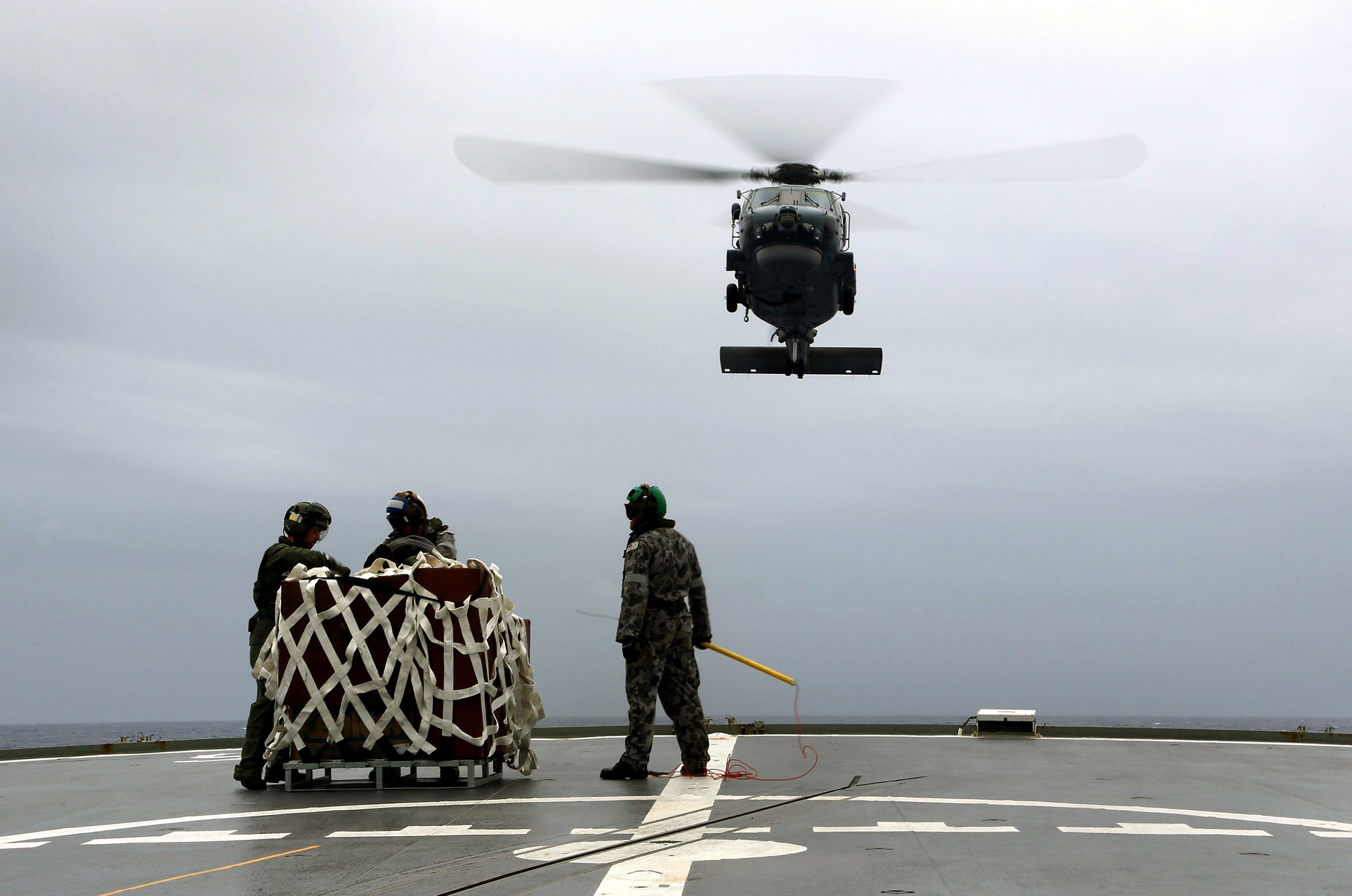 A Seahawk helicopter approaches the flight deck of Australian navy ship H.M.A.S. Toowoomba during a search for the missing Malaysian Airlines Flight 370