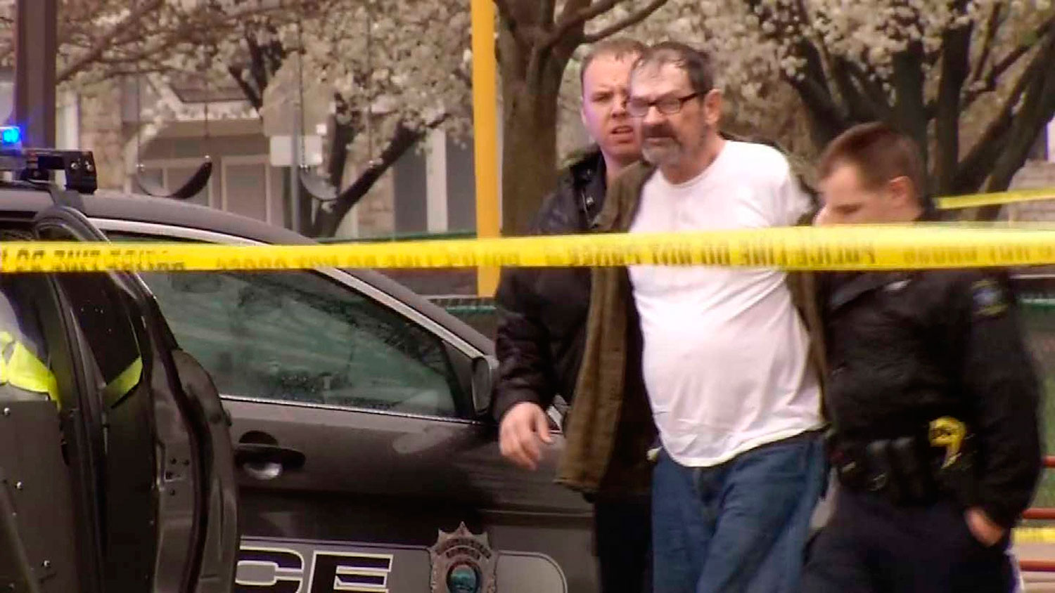 Frazier Glenn Cross, 73, of Aurora, Missouri, is led to a police car after his arrest following shooting incidents which killed three people at two Jewish centers on Sunday in Overland Park, south of Kansas City, Kansas in a still image from video April 13, 2014.