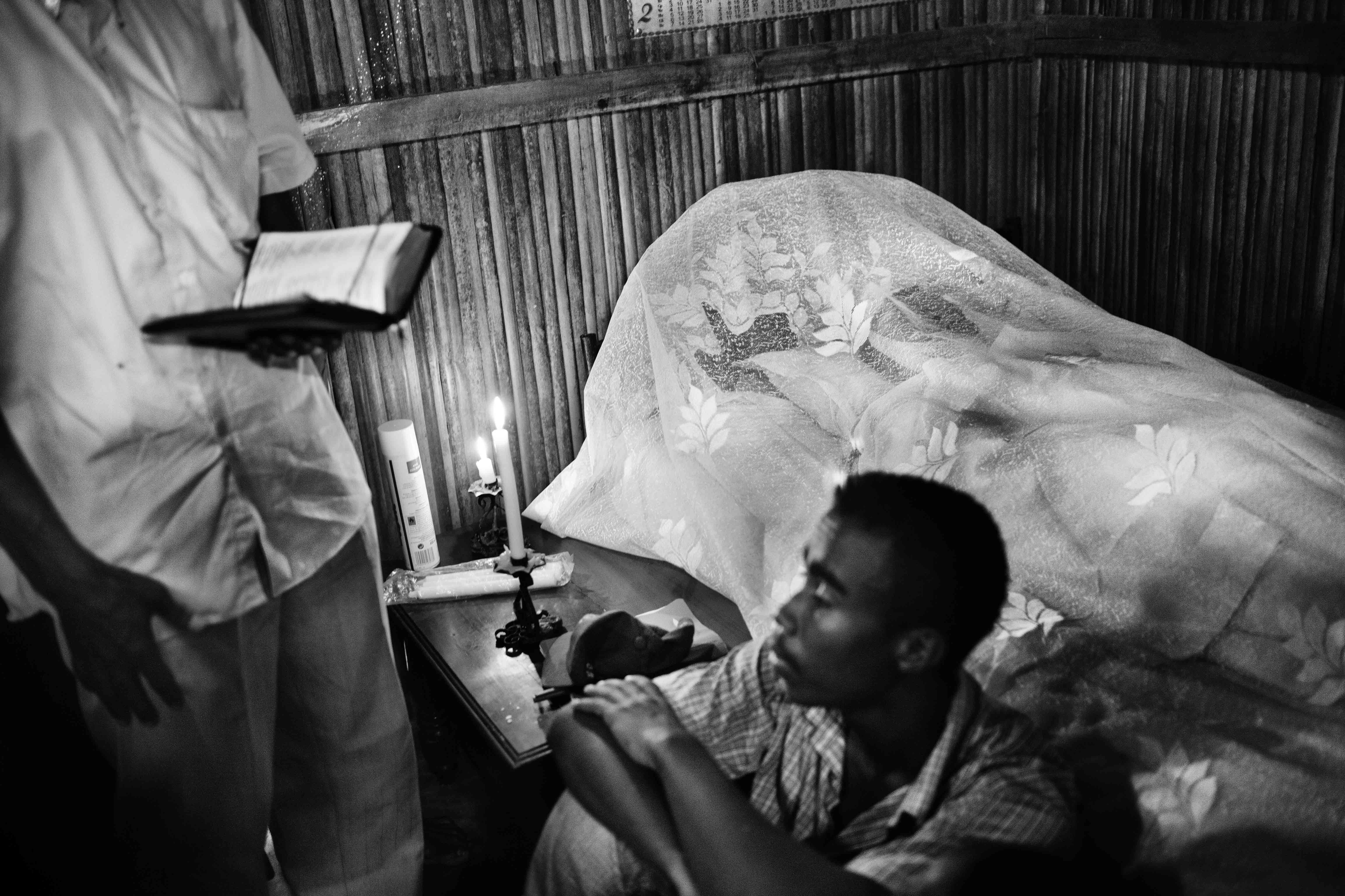 The body of a large plantation's security guard is seen in his bed at home. He was killed by a local gang as revenge for preventing them from stealing cocoa seeds from the plantation the previous day, March 12, 2013. After his death, police launched an operation to try to clamp down on cocoa gangs.