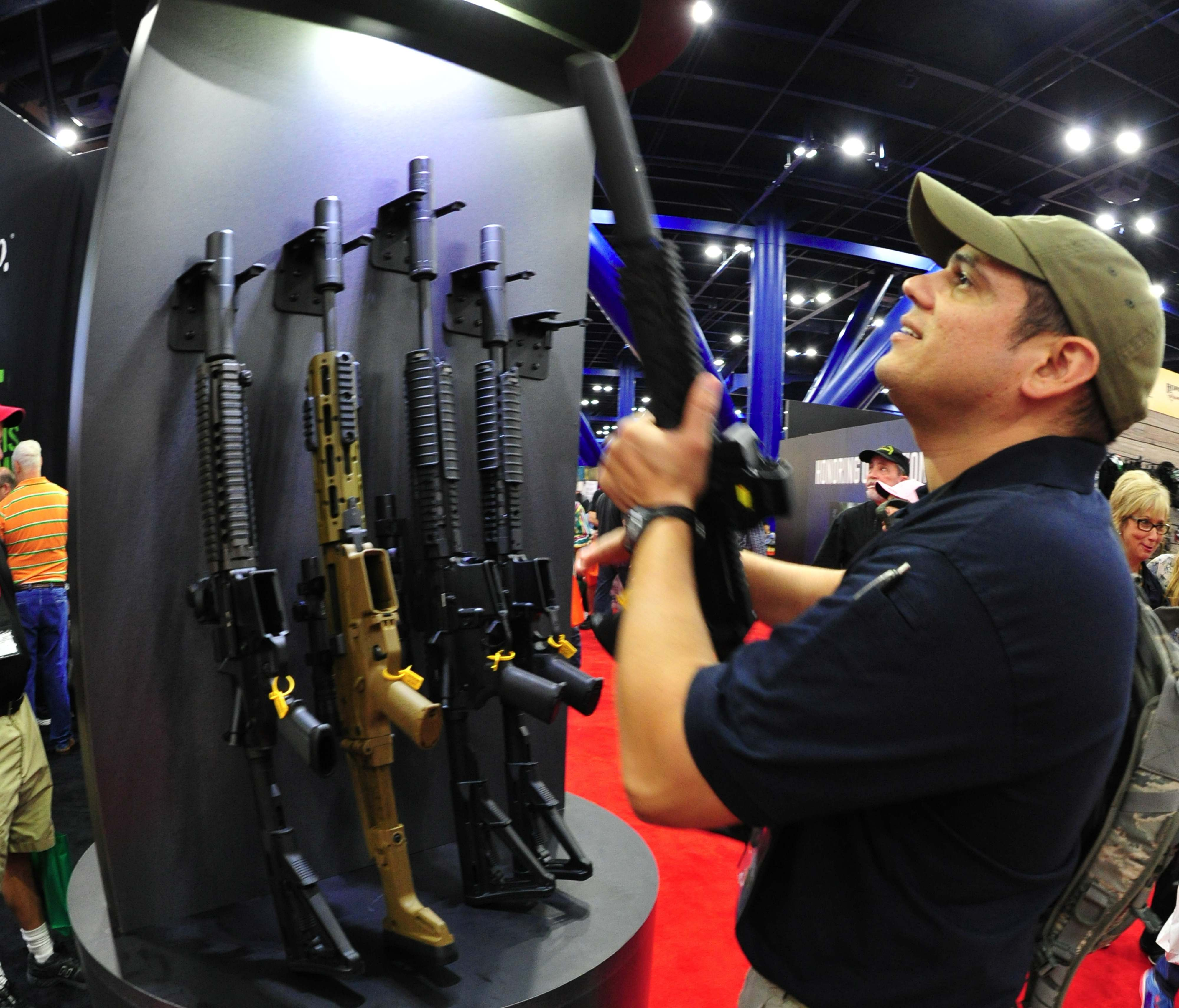 A convention goer picks up a weapon equipped with a silencer during the 142nd annual National Rifle Association(NRA) Convention at the George R. Brown Convention Center May 4, 2013 in Houston, Texas.