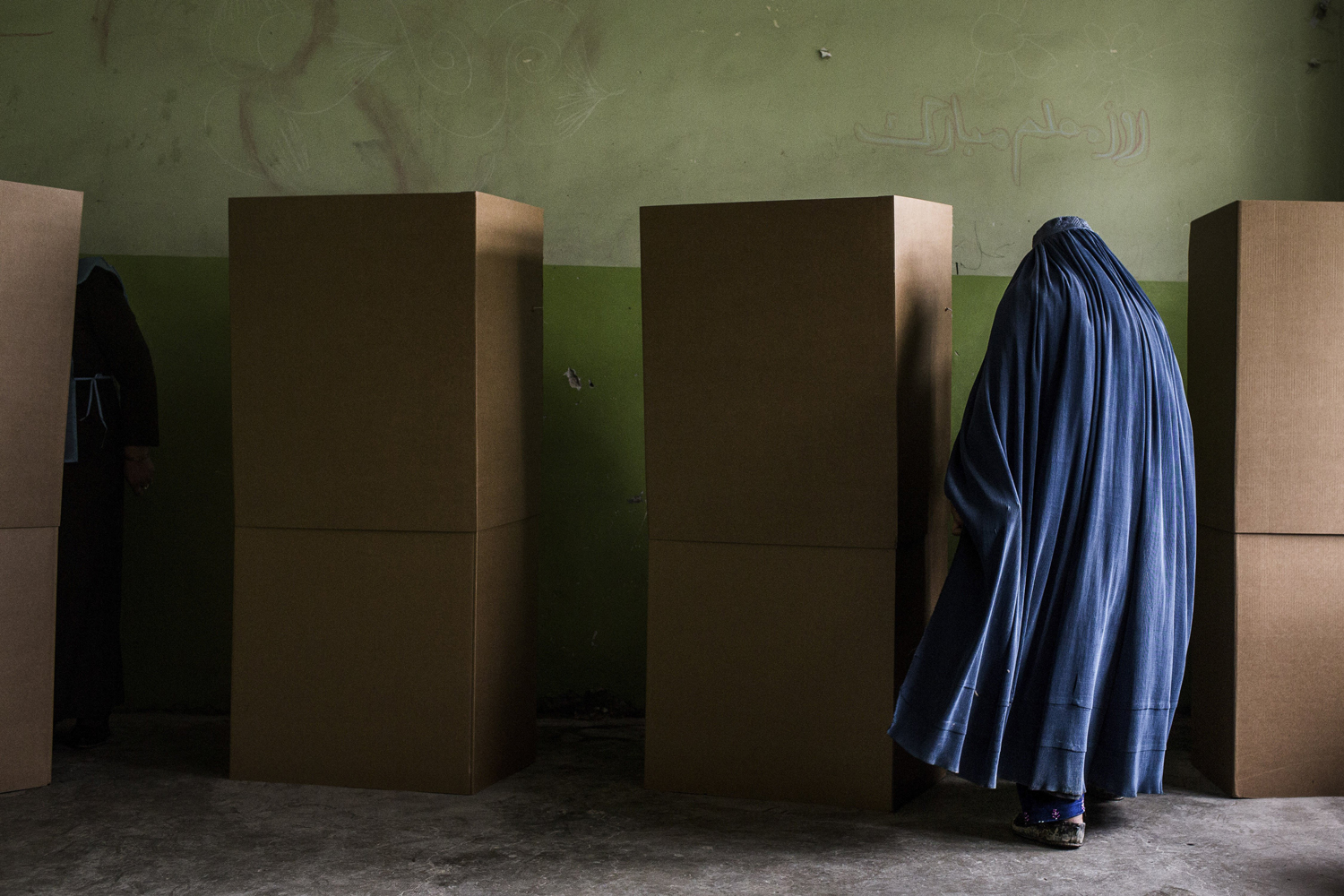 Apr. 5, 2014. A voter prepares to fill out her ballot at a school in Kabul, Afghanistan. Voting hours for the country's general election were extended nationwide due to longer-than-expected lines, and though widespread fears of the Taliban kept roughly one in eight polling centers closed, no heavy attacks had taken place.