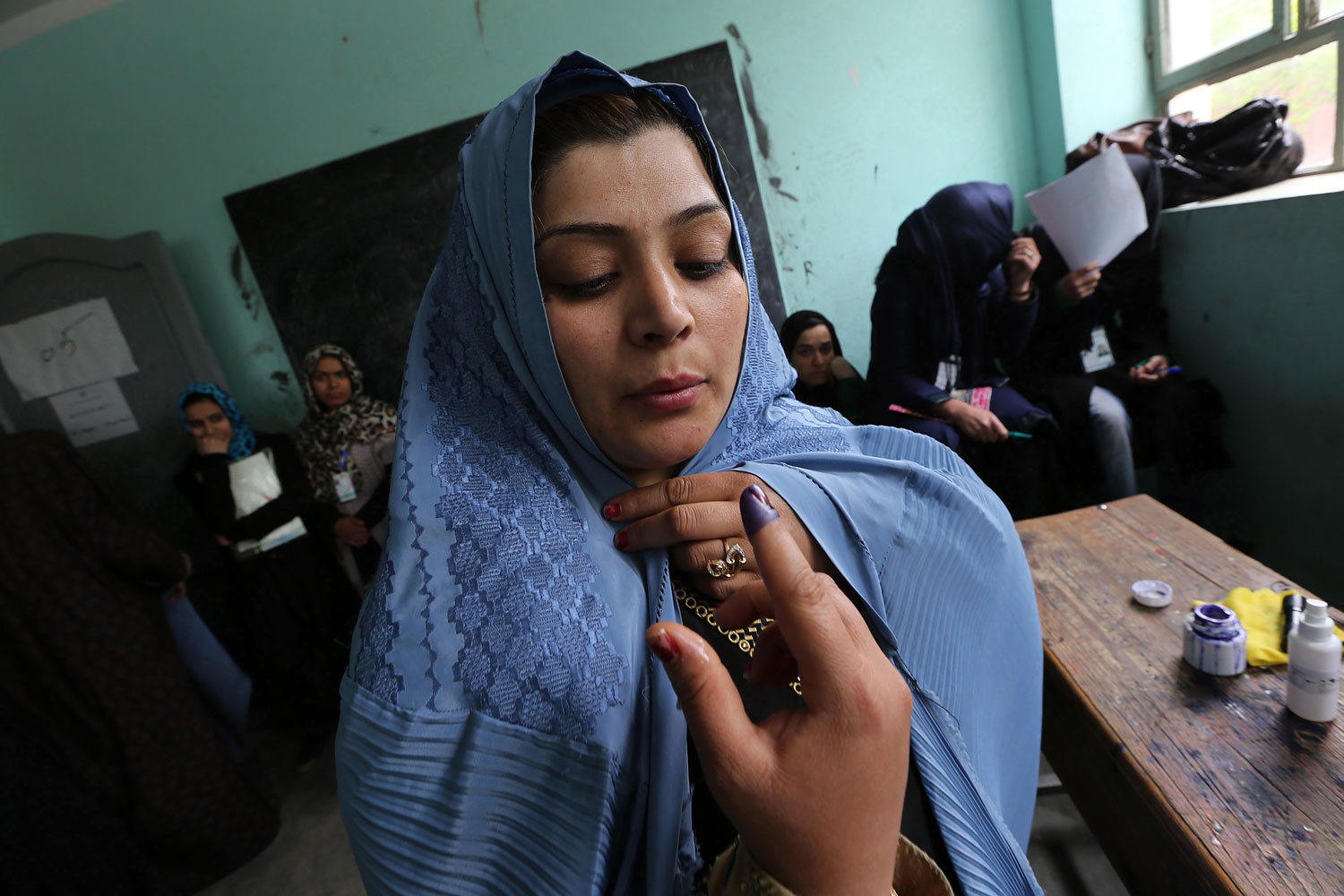 An Afghan voter dries her finger marked with indelible ink after casting her ballot at a polling station in Herat.