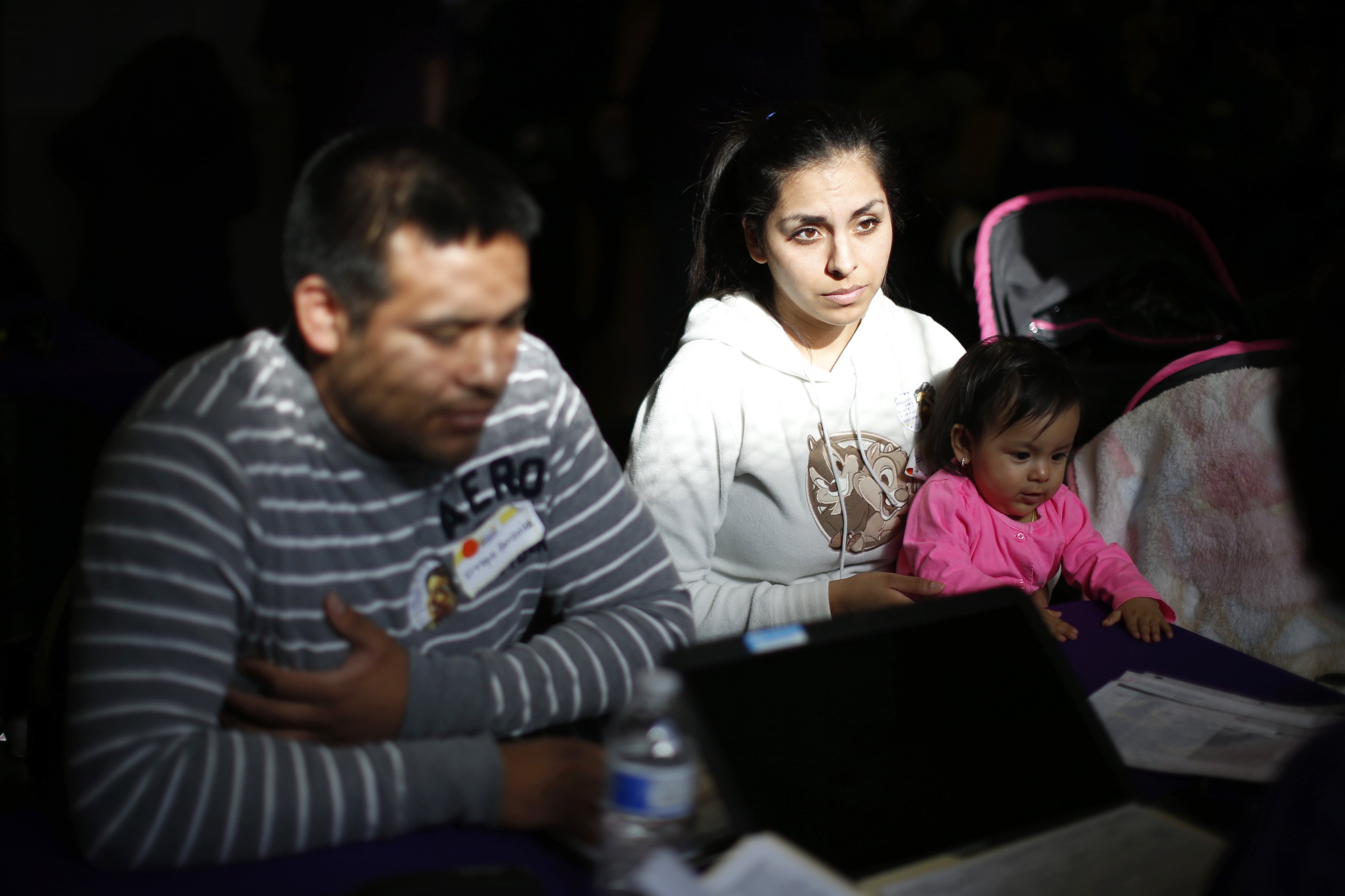 From left: Enrique Gonzalez, 22, Janet Regalado, 21, and their nine-month-old daughter Kayleen Gonzalez sign up for health insurance at an enrolment event in Commerce, Calif., on March 31, 2014.