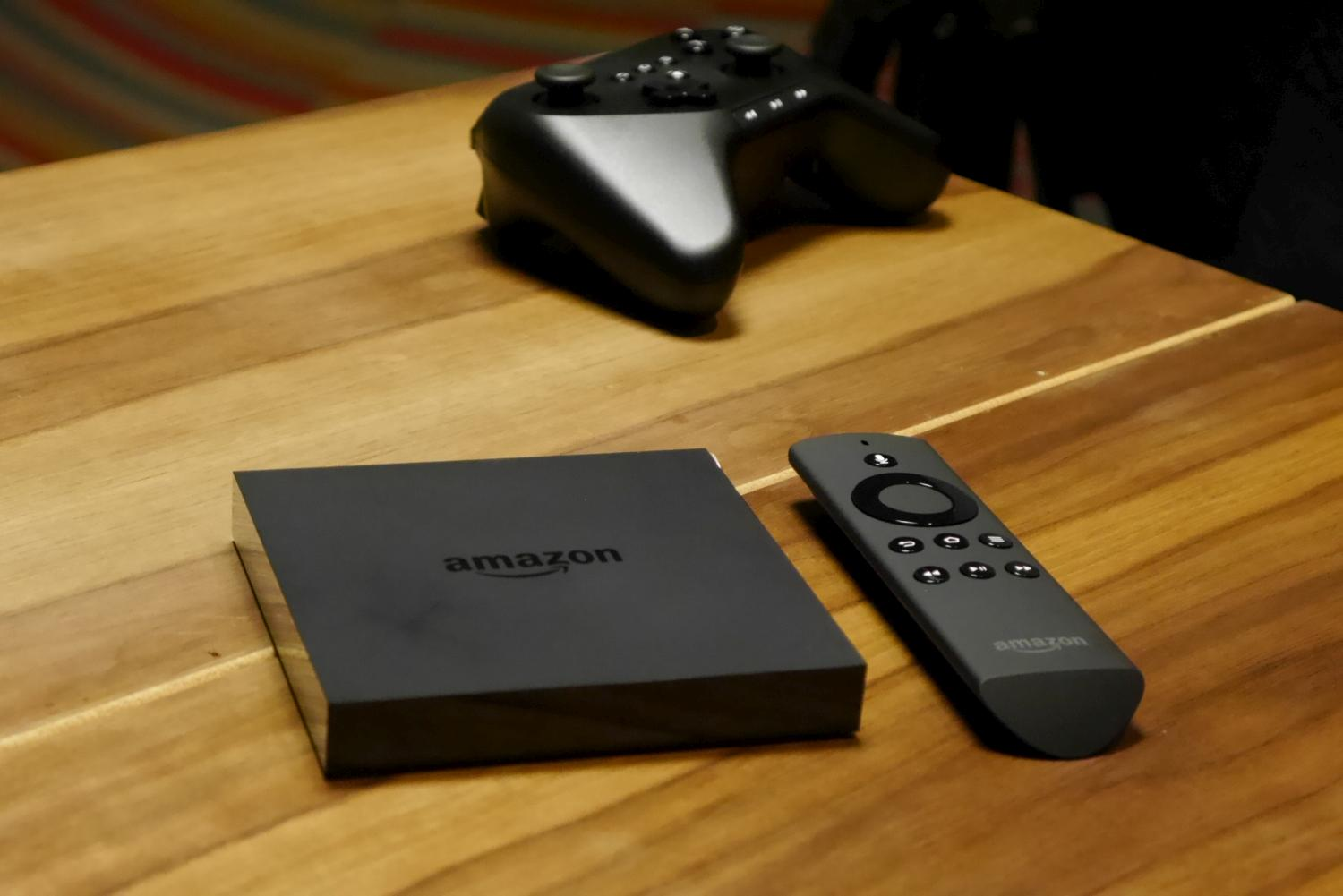 The Fire TV box is about the thickness of a dime turned on its side. Also shown are the included remote control and the $40 gamepad.