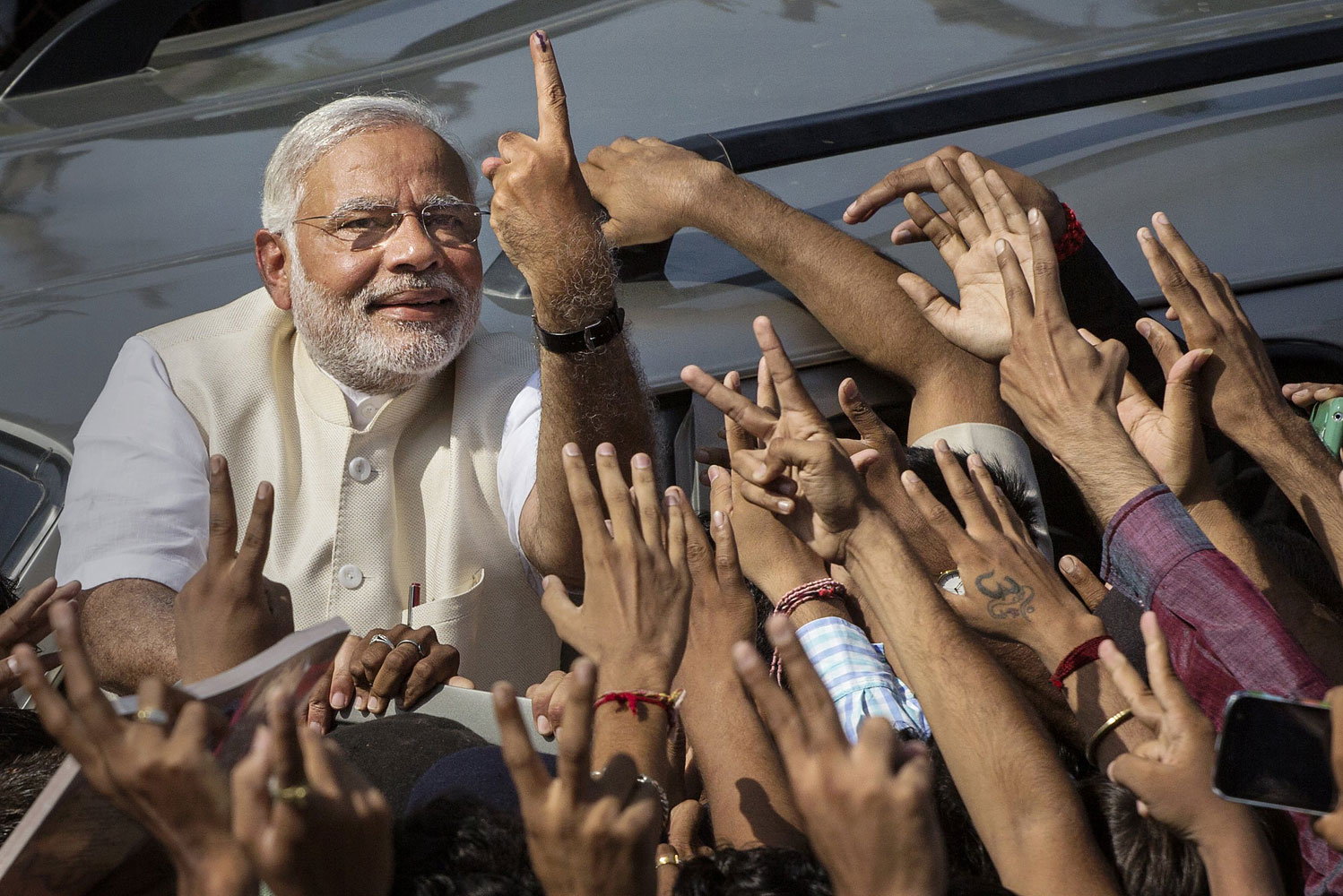BJP leader Narendra Modi shows his inked finger to supporters as he leaves a polling station after voting on April 30, 2014 in Ahmedabad, India.