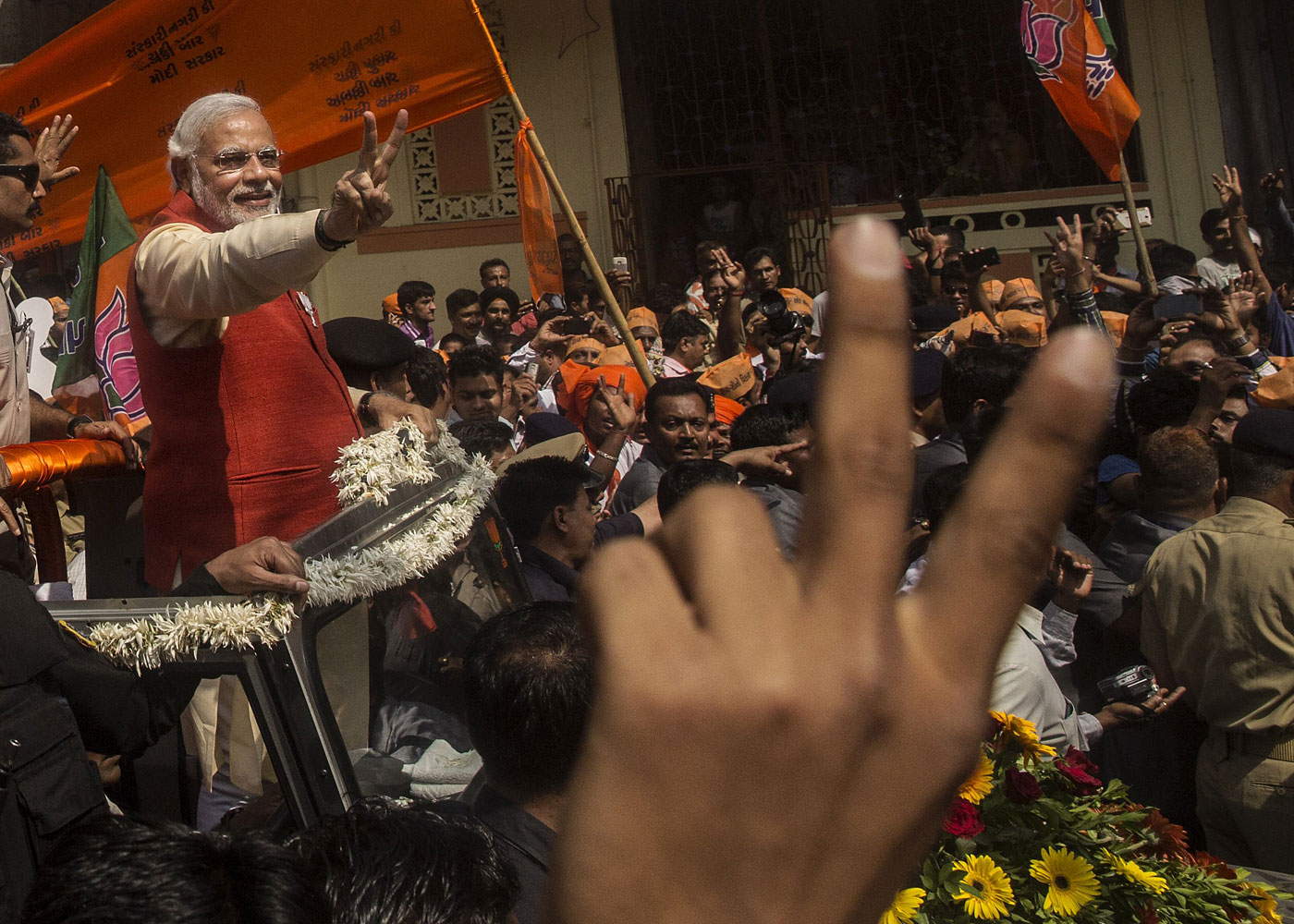 Bharatiya Janata Party leader Narendra Modi gestures to supporters as he rides in an open jeep on his way to file nomination papers on April 9, 2014 in Vadodra, India.