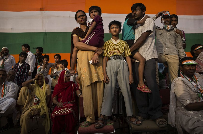 An Indian family listens as Rahul Gandhi, leader of India's ruling Congress Party speaks at a rally on April 6, 2014 in New Delhi.