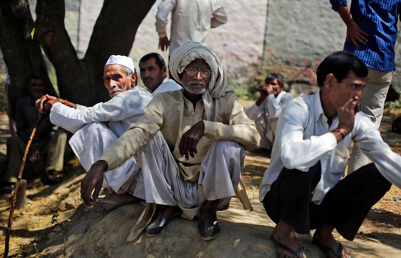 Indian villagers sit outside a polling station in Kutba village, Muzaffarnagar, in the northern Indian state of Uttar Pradesh,  April 10, 2014.