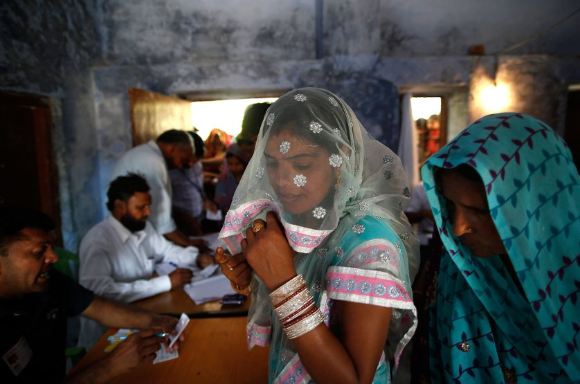 Female voters wait for their identities to be verified before being allowed to vote in Ujina, in the Indian state of Haryana, April 10, 2014.