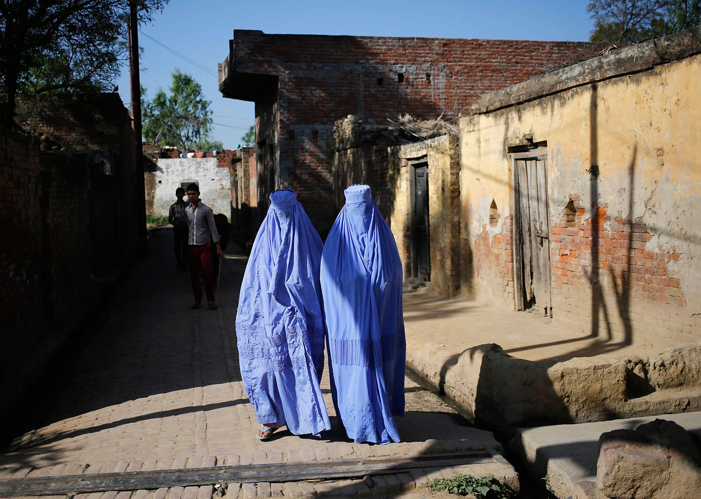 Muslim women, who were displaced by deadly religious strife last year, walk back to their relief camp after casting their vote for the general election at a polling station in Palra village in Muzaffarnagar district in the northern Indian state of Uttar Pradesh, April 10, 2014.
