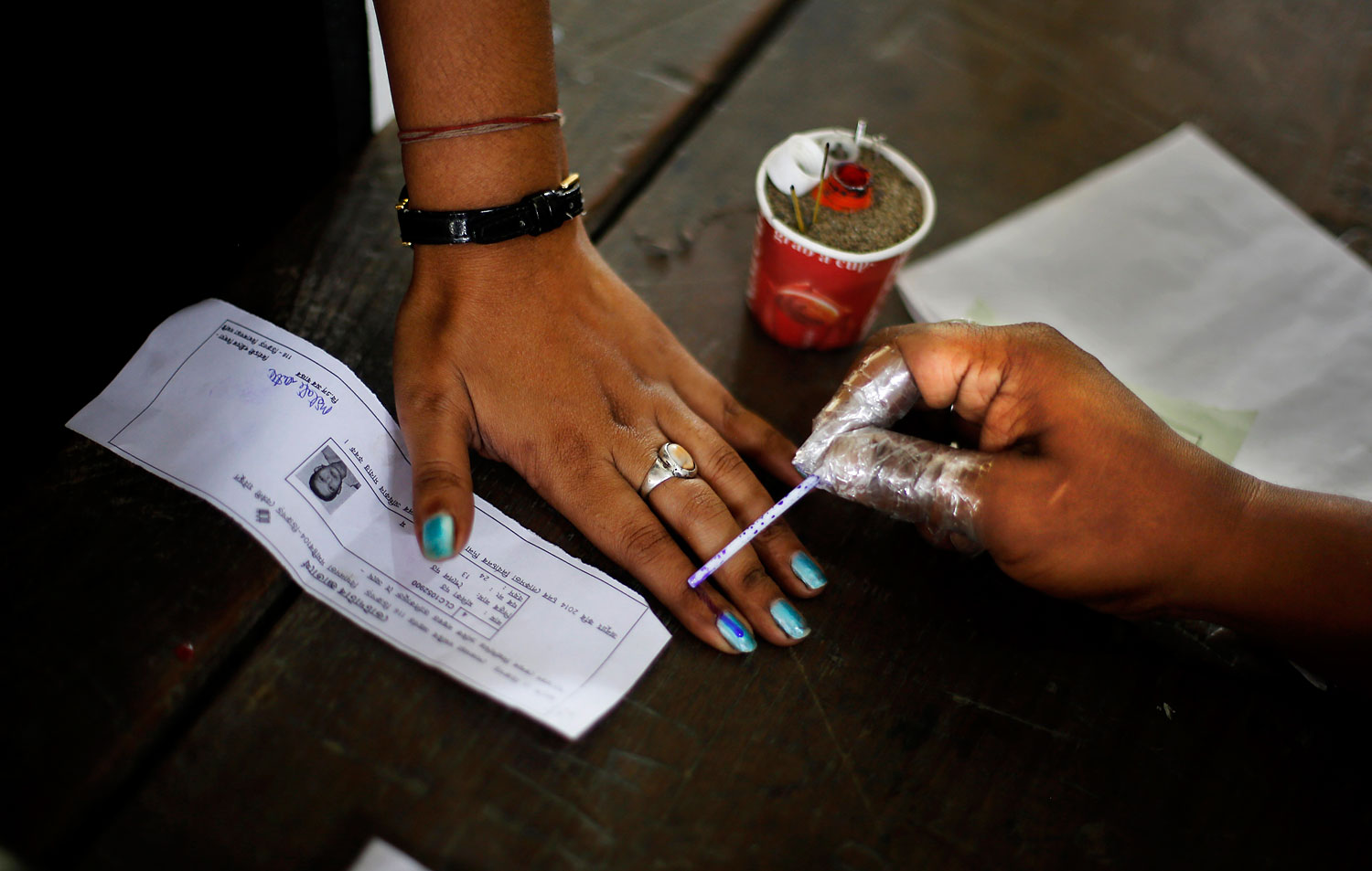 An Indian election officer applies an indelible ink mark on the finger of a woman during the first phase of elections in Dibrugarh, in the northeastern state of Assam, India, April 7, 2014.