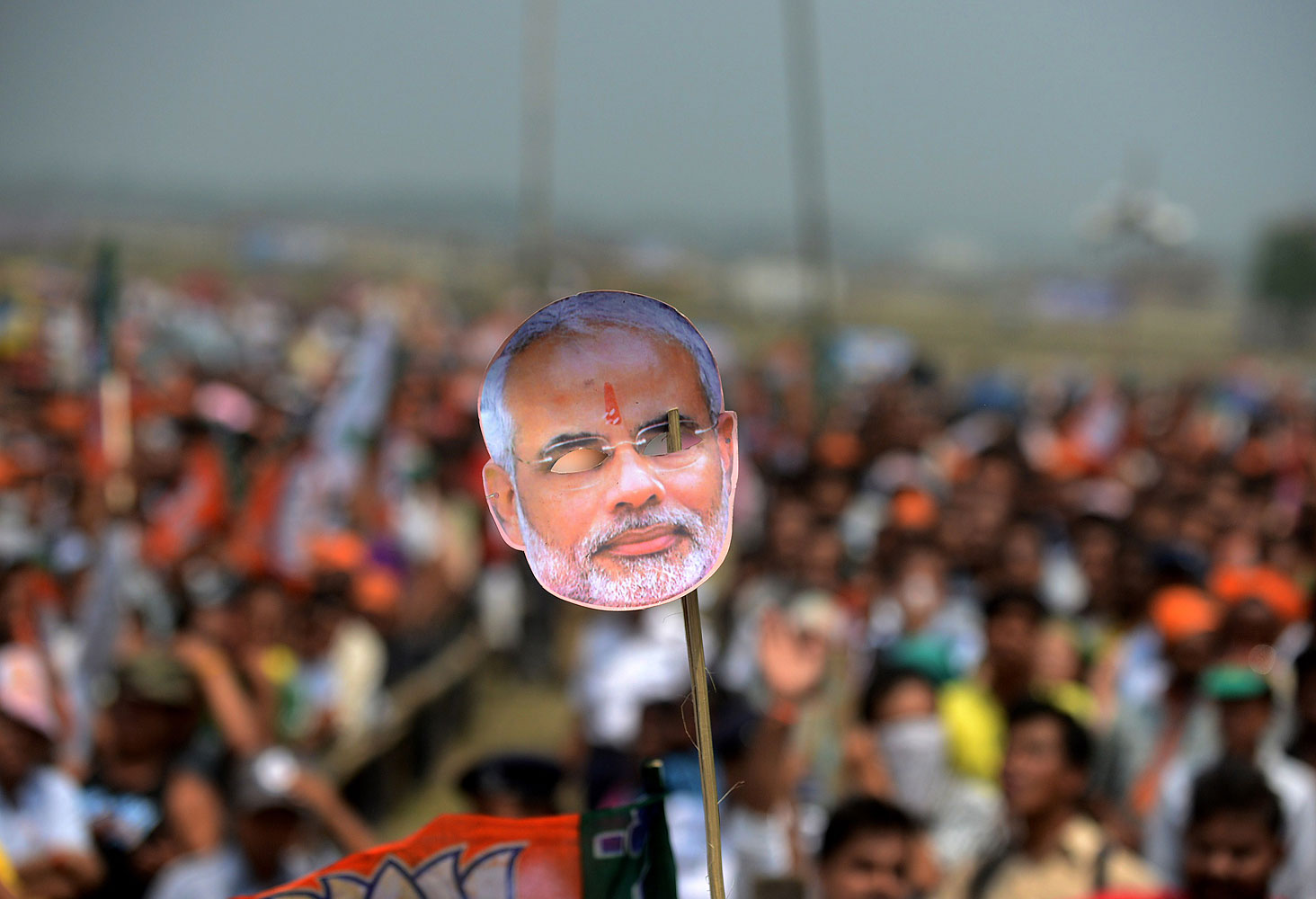 An Indian supporter holds a mask of Chief Minister of the western Gujarat state and Bharatiya Janata Party Prime Ministerial candidate, Narendra Modi during an election campaign rally for the support of BJP candidate for Darjeeling constituency, S S Ahluwalia on the outskirts of Siliguri on April 10, 2014.