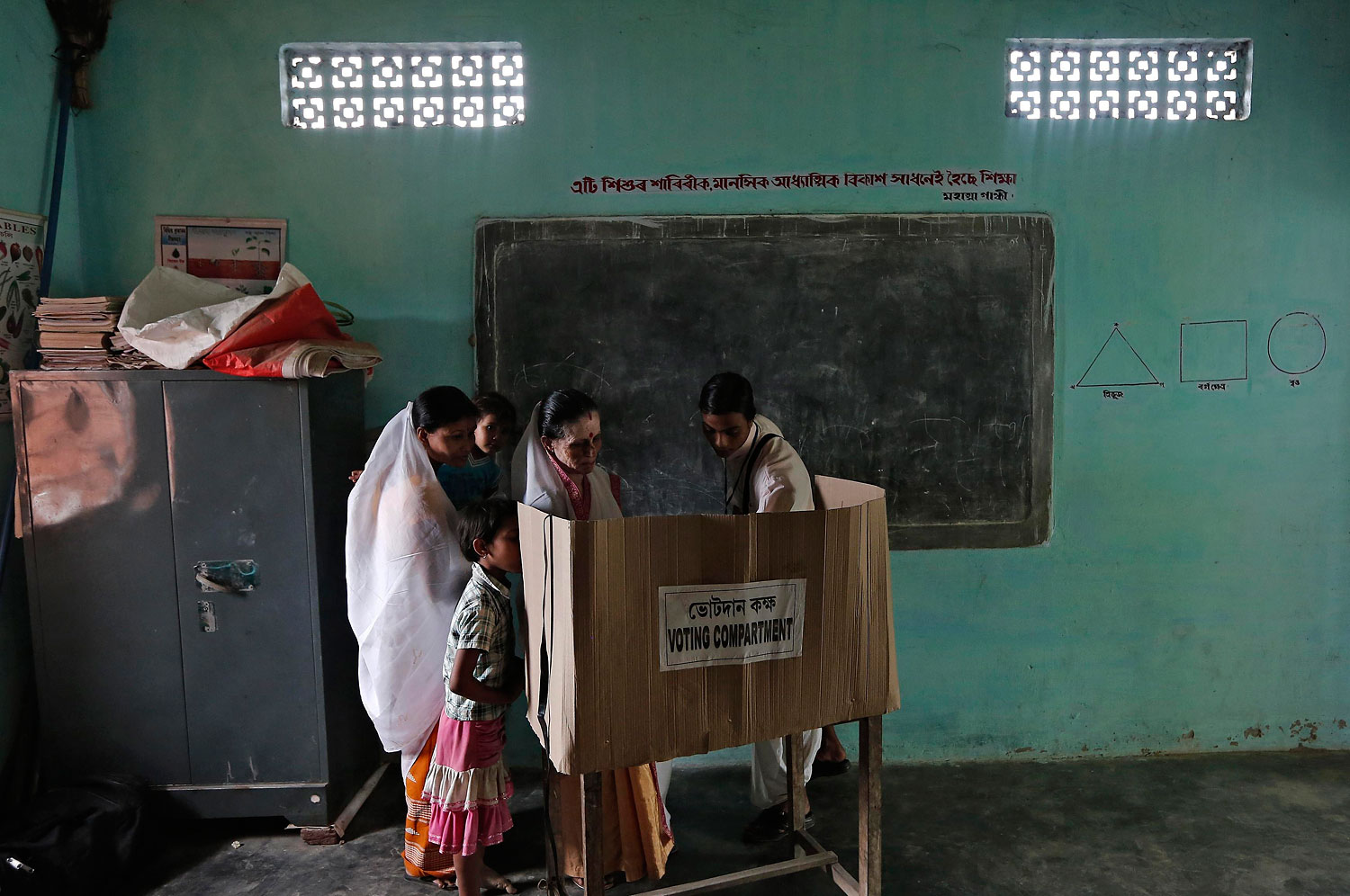 A polling officer helps a woman to cast her vote at a polling station in Majuli, a large river island in the Brahmaputra river, Jorhat district, in the northeastern Indian state of Assam, April 7, 2014.