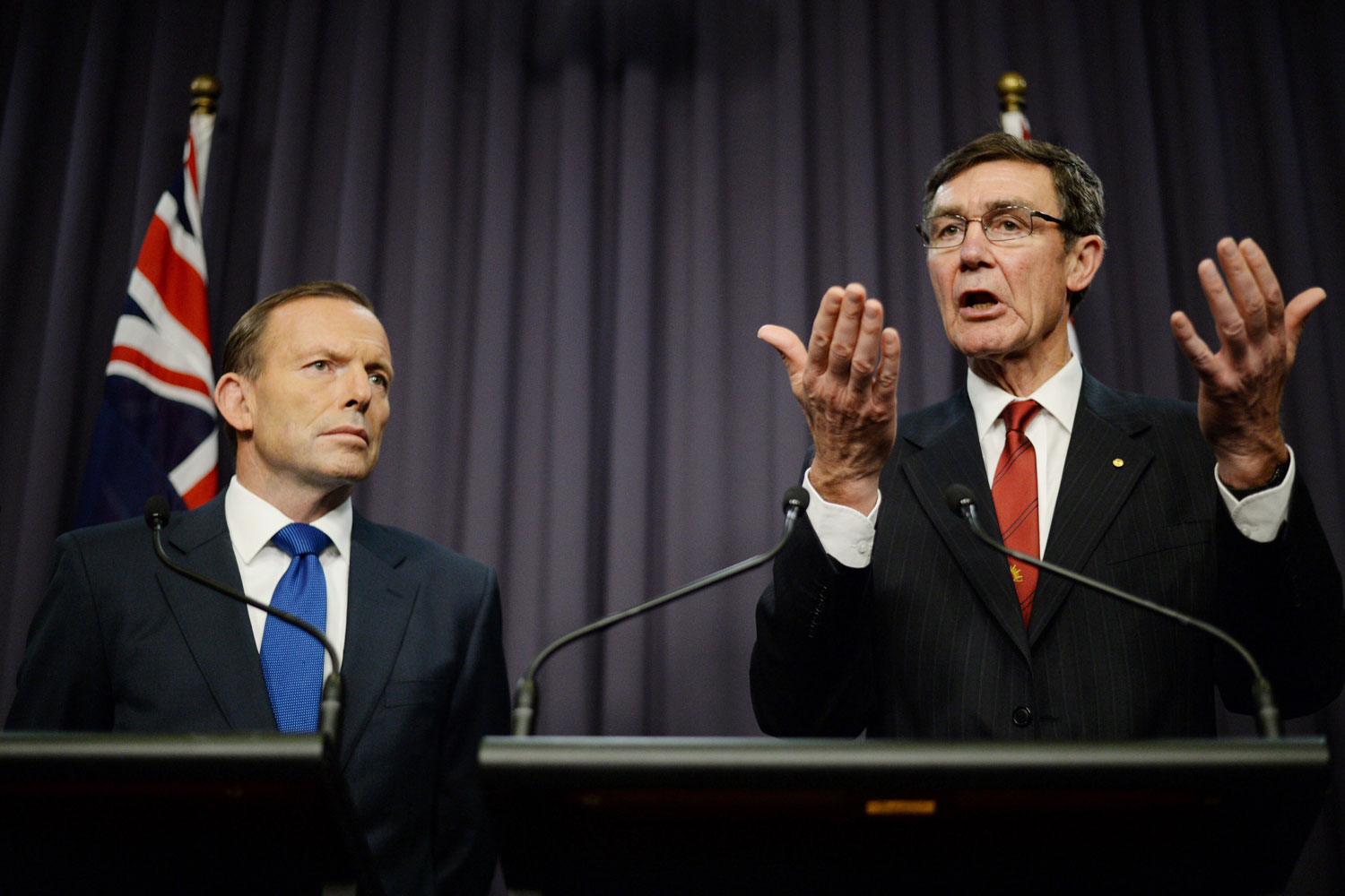 From left: Prime Minister Tony Abbott listens as Angus Houston, in charge of joint search efforts, speaks to the media during a press conference at Parliament House in Canberra on April 28, 2014.