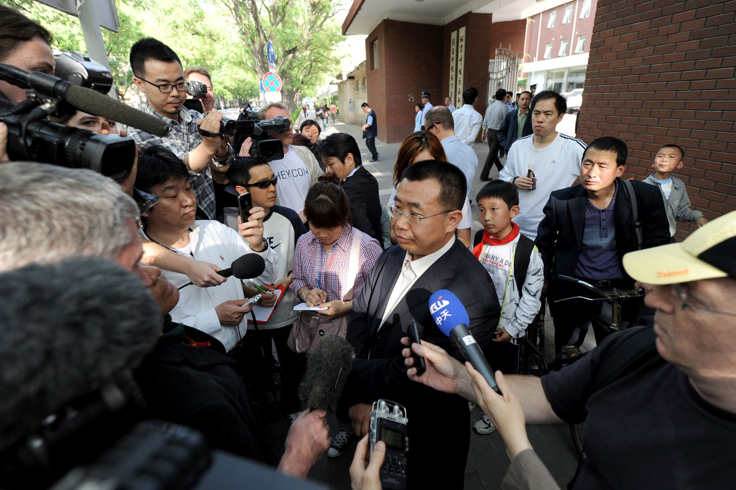 Journalists interview Chinese rights lawyer Jiang Tianyong at a gate of the Chaoyang hospital in Beijing in Beijing on May 2, 2012.