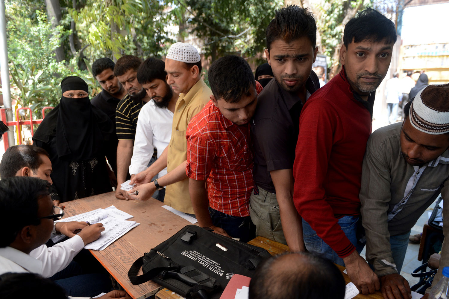 Indian polling officials check the details of voters at a polling station in New Delhi on April 10, 2014.