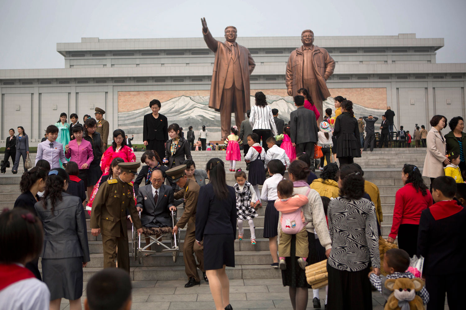 North Koreans arrive at Pyongyang's Mansu Hill to pay their respects to bronze statues of the late leaders Kim Il Sung and Kim Jong Il at Munsu Hill in Pyongyang on Tuesday, April 15, 2014, the official birthday of Kim Il Sung.