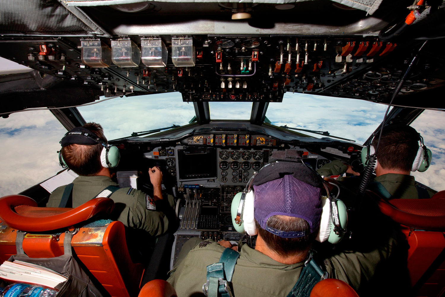 Co-Pilot Flying Officer Marc Smith (L) and crewmen fly at high altitude aboard a Royal Australian Air Force (RAAF) AP-3C Orion aircraft after searching for the missing Malaysian Airlines Flight MH370 over the southern Indian Ocean March 24, 2014.