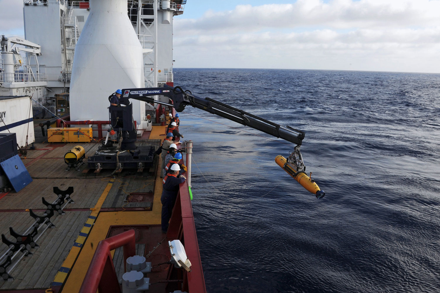 Crew aboard the Australian Defence Vessel Ocean Shield move the U.S. Navy's Bluefin-21 autonomous underwater vehicle into position for deployment in the southern Indian Ocean to look for the missing Malaysia Airlines flight MH 370, April 14, 2014.
