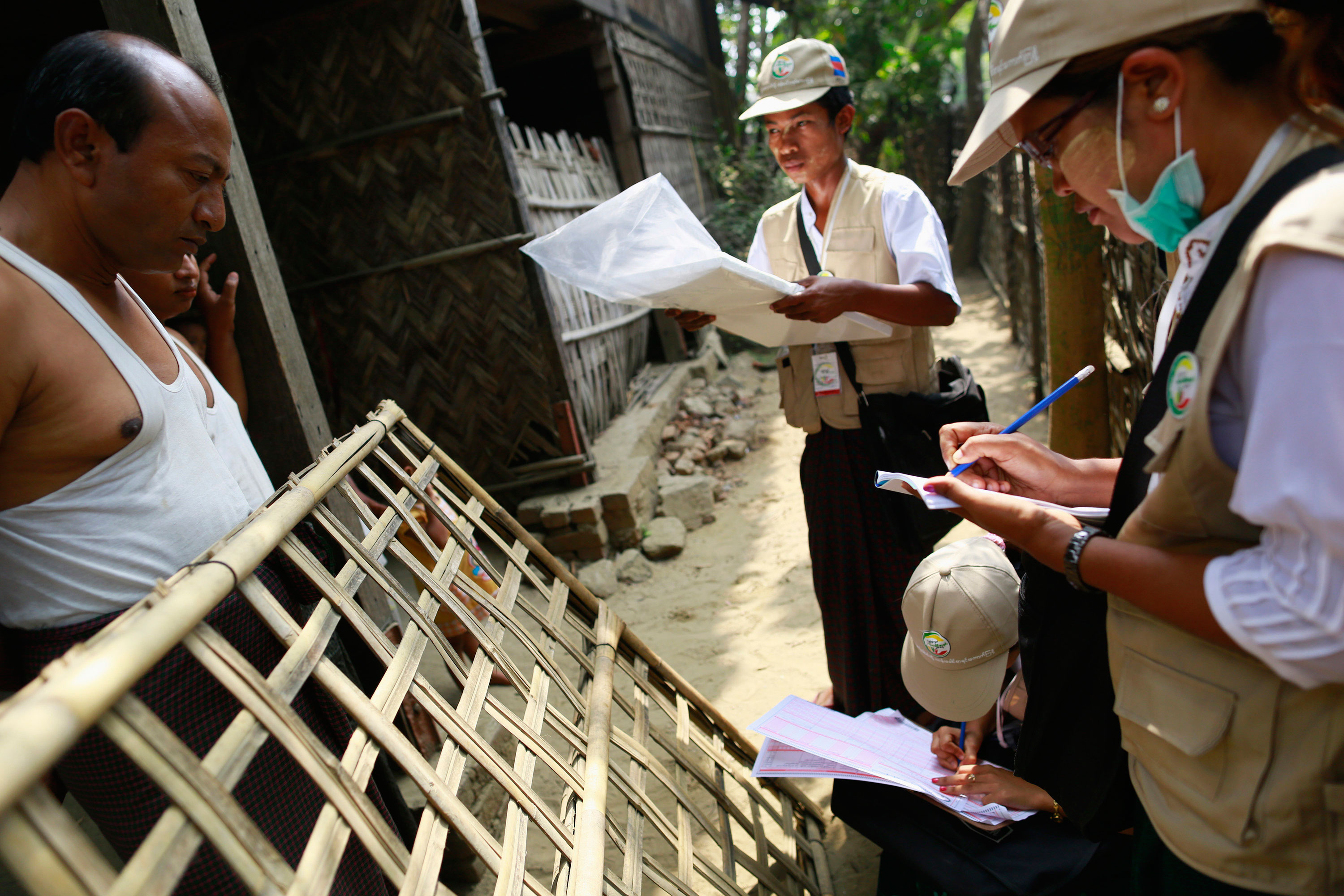 Burmese volunteers speak to a family during a national census at a Rohingya village in Sittwe on March 31, 2014