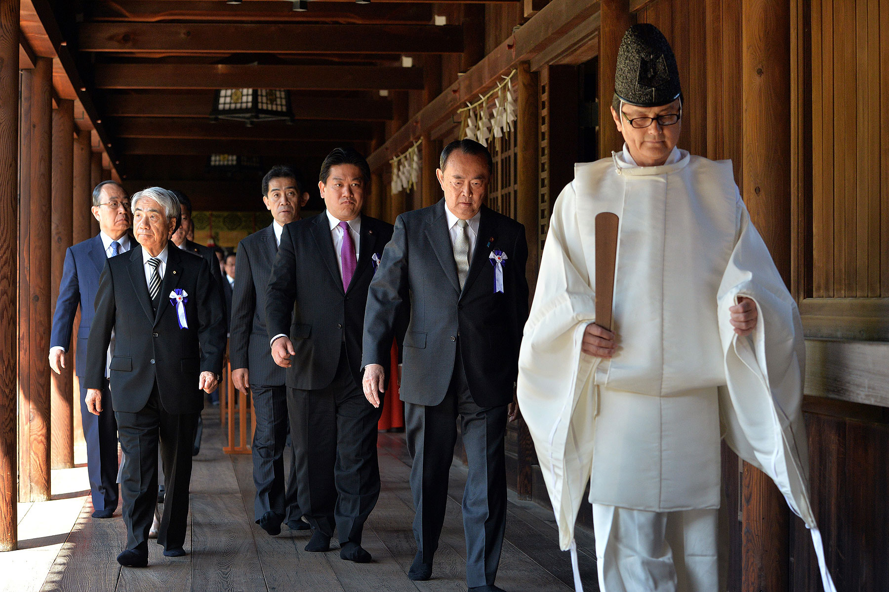 Japanese lawmakers follow a Shinto priest during a visit to the controversial Yasukuni Shrine to honor war dead during a spring festival in Tokyo on April 22, 2014
