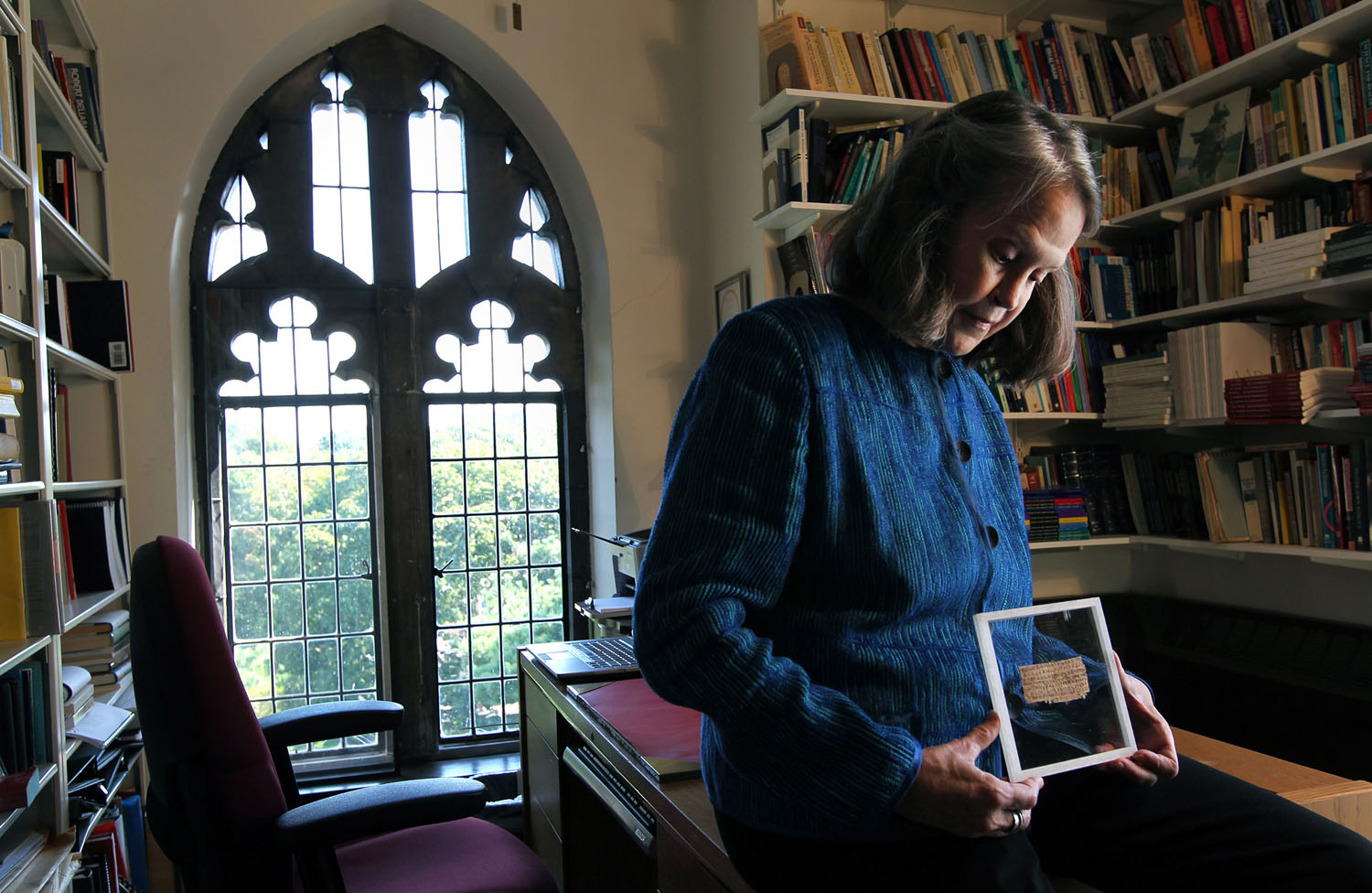 Karen L. King Hollis, Professor of Divinity at Harvard University, in her office with a papyrus fragment of the gospel of Jesus' wife.