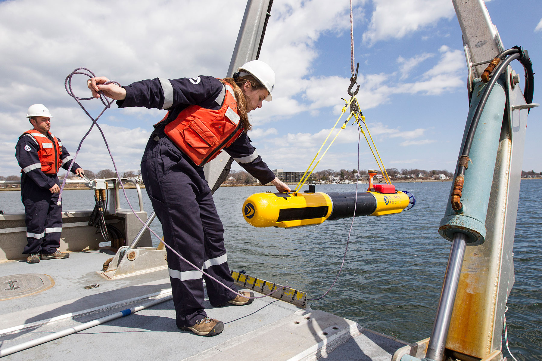 A submarine built by Bluefin Robotics is lowered into the water by a systems engineer in Quincy, Mass., April 9, 2014