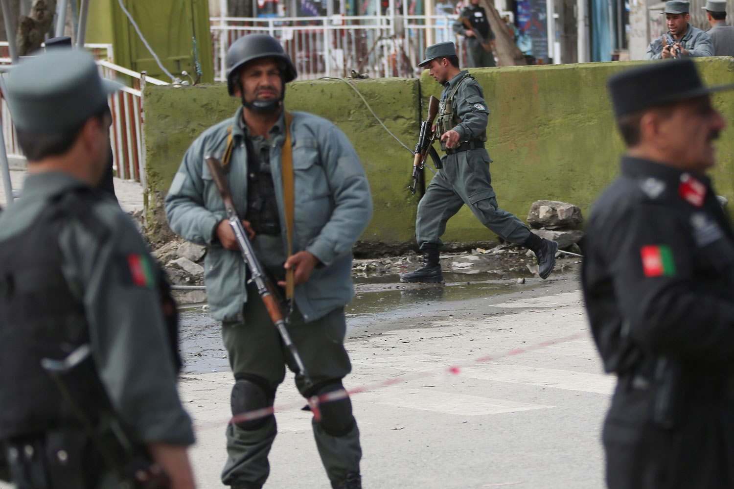 Afghan police men block the street after a suicide bomber wearing a military uniform struck the entrance gate of the Interior Ministry compound in Kabul, April 2, 2014.